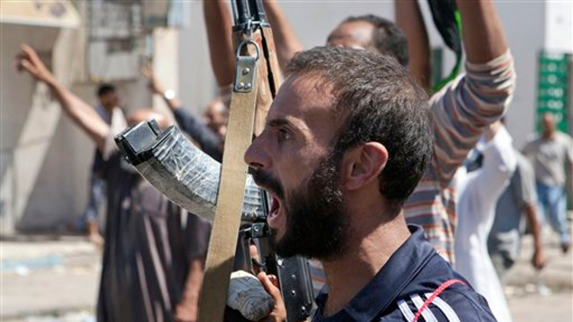 Aug. 14: In this photo, a Libyan rebel fighter in Zawiya, western Libya, reacts to the news that the city of Surman, an important strategic point, is now under the control of the rebel forces.  Libyan rebels have claimed they were trying to cut off two key supply routes to Muammar al-Qaddafi's stronghold in Tripoli after capturing more towns in the west of the country.
