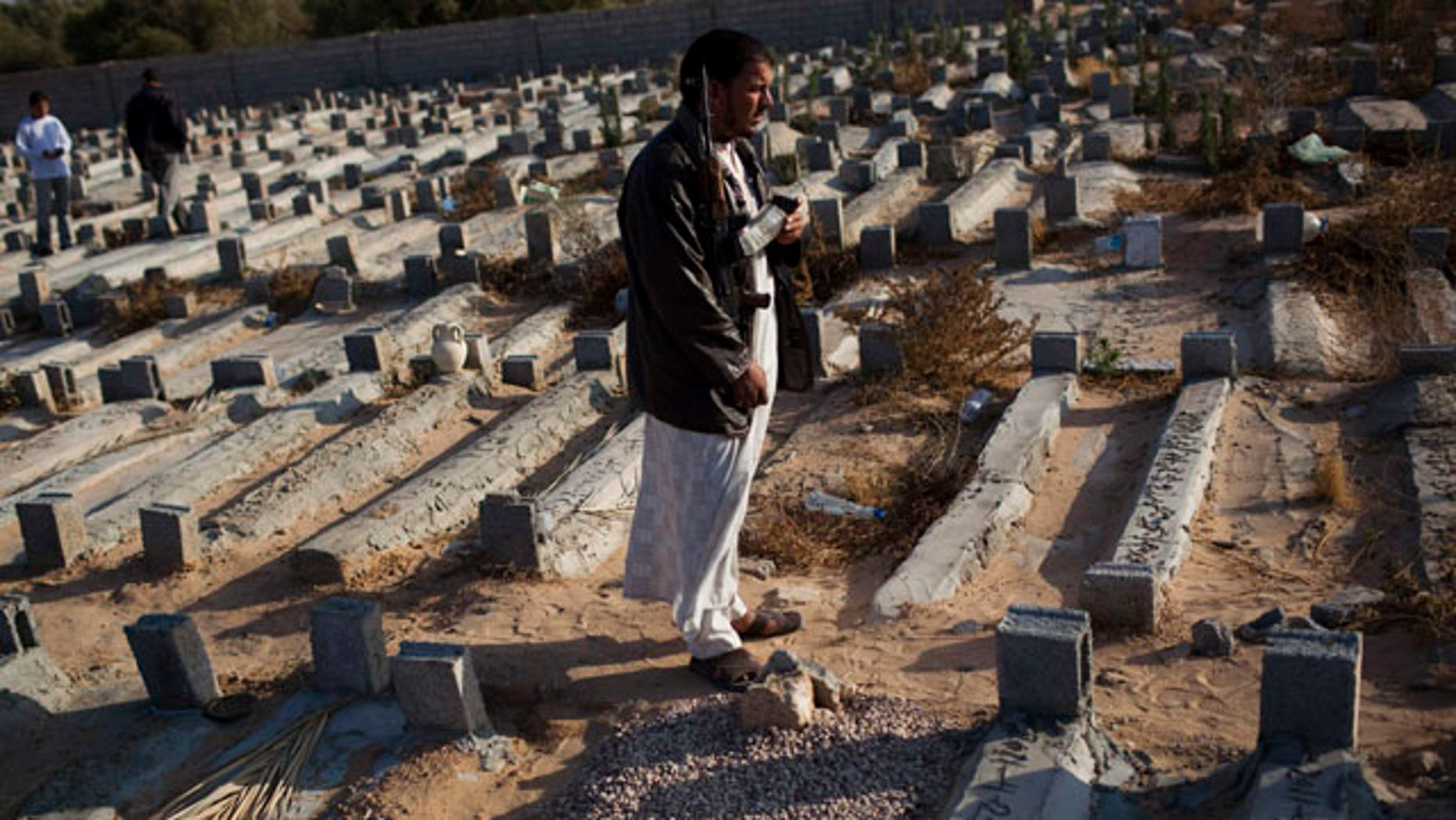 May 26: Faissel Omran Dehik stands next to the tomb of his brother who was killed a week ago during fighting against Qaddafi forces on the outskirts of Misrata, Libya. For the first time, pro-Qaddafi forces expressed interest to speak with the rebels.