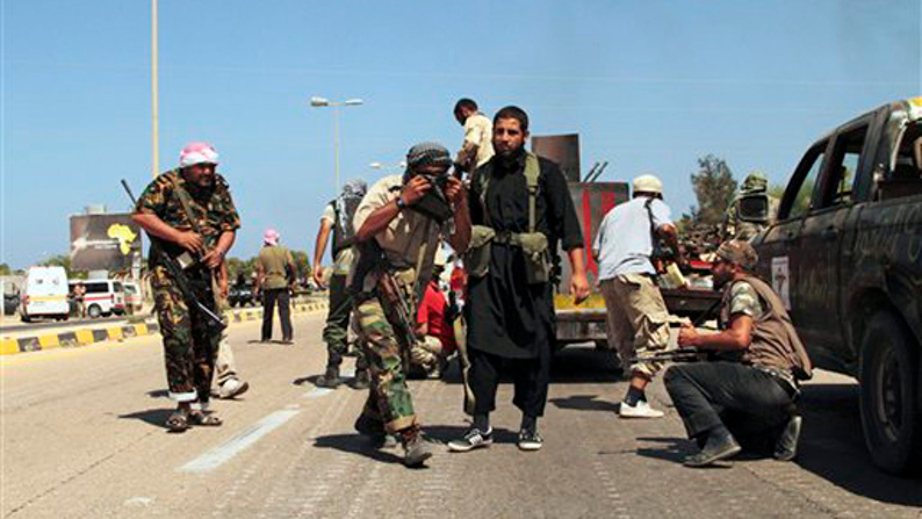 Revolutionary fighters take cover from heavy artillery, rocket and missile counter-attacks launched by Qaddafi loyalists in Sirte, Libya, Saturday, Sept. 24, 2011