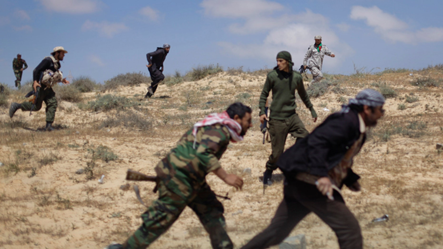 April 4: Rebel fighters run for cover from incoming shelling by pro-Qaddafi forces, near the front line in Brega, Libya. Libyan rebels pushed into the strategic oil town of Brega on Monday but came under fire from Muammar Qaddafi's forces, as a government envoy began a diplomatic push in Europe to discuss an end to the fighting. (AP)
