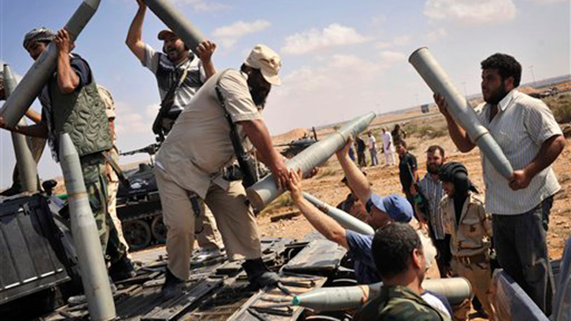Libyan revolutionary fighters load munitions to be fired during an attack for the city of Sirte, Libya, Wednesday, Oct. 5, 2011.