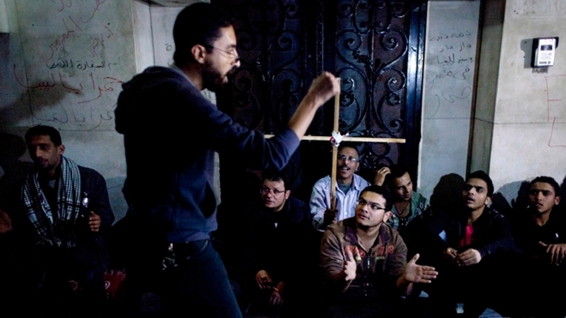 Egyptian protesters sit near Libyan embassy during demonstration condemning the death of Egyptian Christian Ezzat Atallah at a Libyan prison earlier this month. Four Christians remain imprisoned in Libya, including an American (AP Photo/Nasser Nasser)