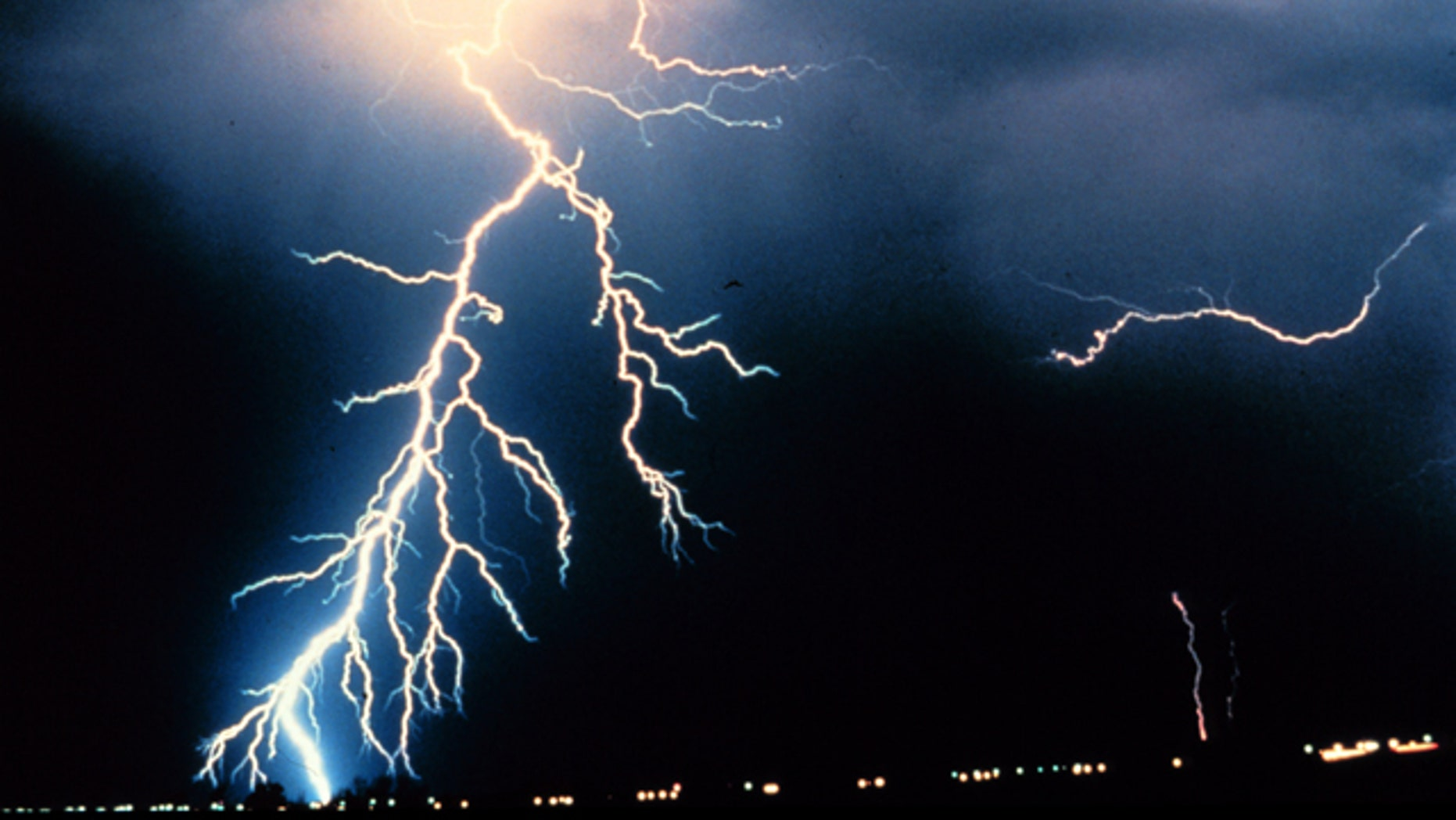 Multiple cloud-to-ground and cloud-to-cloud lightning strokes during night-time.