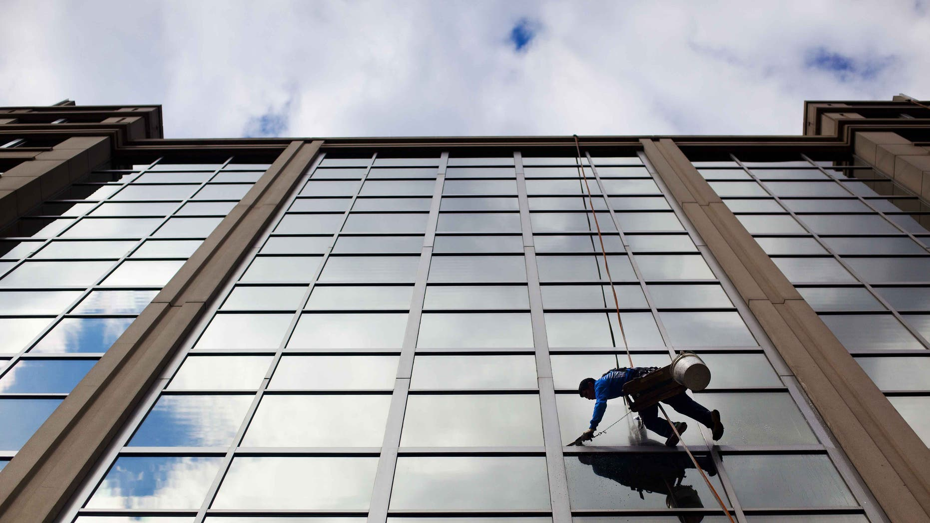 FILE - In this April 23, 2015 file photo, a window washer cleans the windows of an office building in downtown Washington. The U.S. government issues the May jobs report on Friday, June 5, 2015. (AP Photo/Pablo Martinez Monsivais, File)