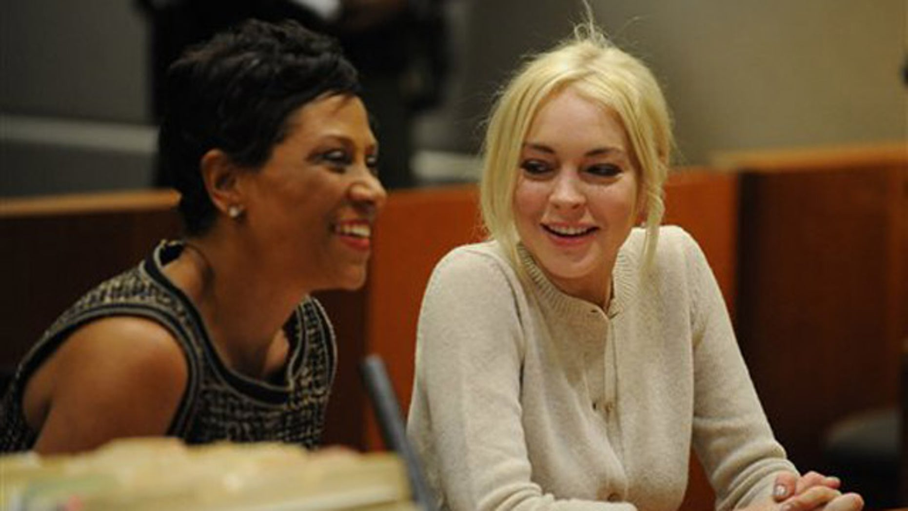 Lindsay Lohan, right, alongside her attorney Shawn Chapman Holley are seen during progress report session at the Los Angeles Superior Court Wednesday, Dec. 14, 2011 in Los Angeles. A judge says Lindsay Lohan is doing well under her strict new probation routine of counseling and working at the county morgue. Lohan remains on probation for a 2007 drunken driving and a grand theft case filed earlier this year. (AP Photo/Michael Nelson, Pool)