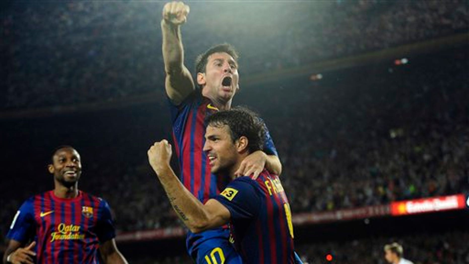 FC Barcelona's Lionel Messi from Argentina, second right reacts after scoring with his teammate Cesc Fabregas against Real Madrid during his Super Cup final second leg soccer match at the Camp Nou Stadium in Barcelona, Spain, Wednesday, Aug. 17, 2011. (AP Photo/Manu Fernandez)