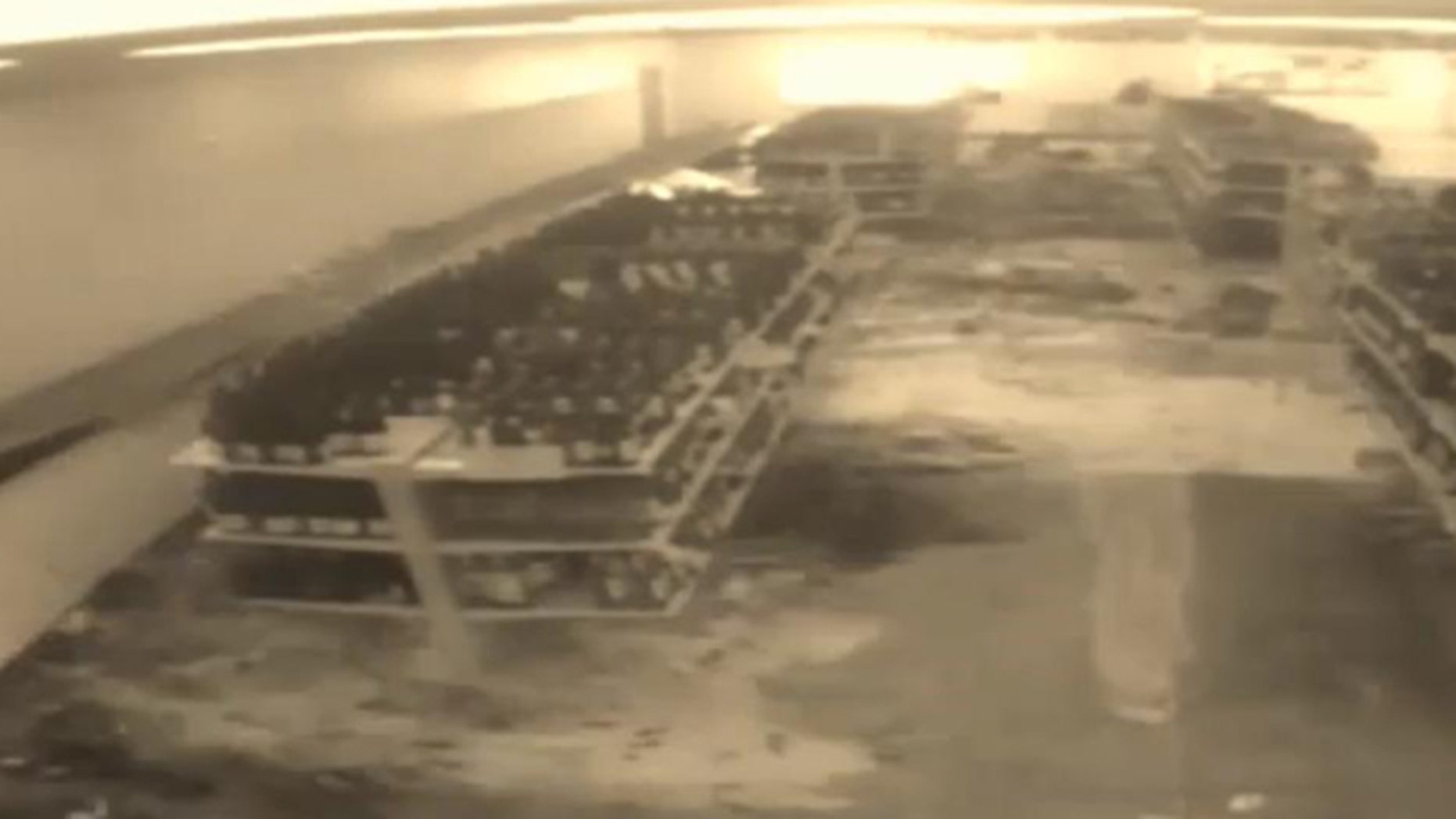 In this image taken from video, a shelf collapses at a liquor store in Sheboygan, Wisc., causing thousands of bottles of wine to shatter.