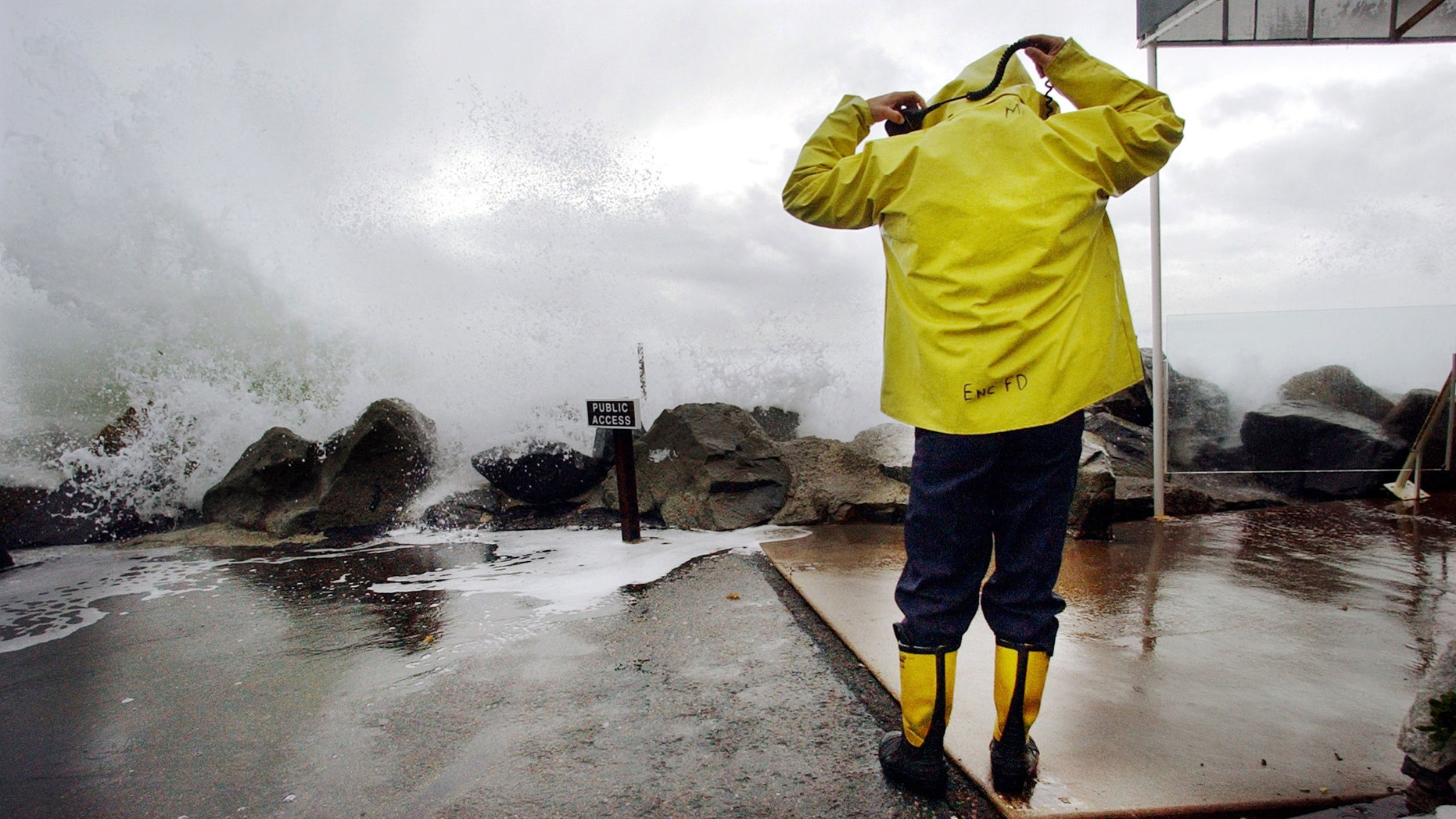 CARDIFF BY THE SEA, CA - DECEMBER 20:  Encinitas fireman Mike Kemp adjusts his hood as a wave crashes over a sea wall December 20, 2002 in Cardiff By the Sea, California. Heavy rains and large surf pounded the West Coast as a product of El Nino with the region expecting above average rainfall totals this winter due to El Nino.  (Photo by Sandy Huffaker/Getty Images)