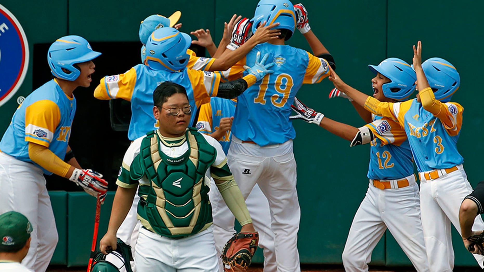 Mana Lau Kong (19) celebrates with his teammates after hitting a home run in the bottom of the first inning of Sunday's Little League World Series Championship game.