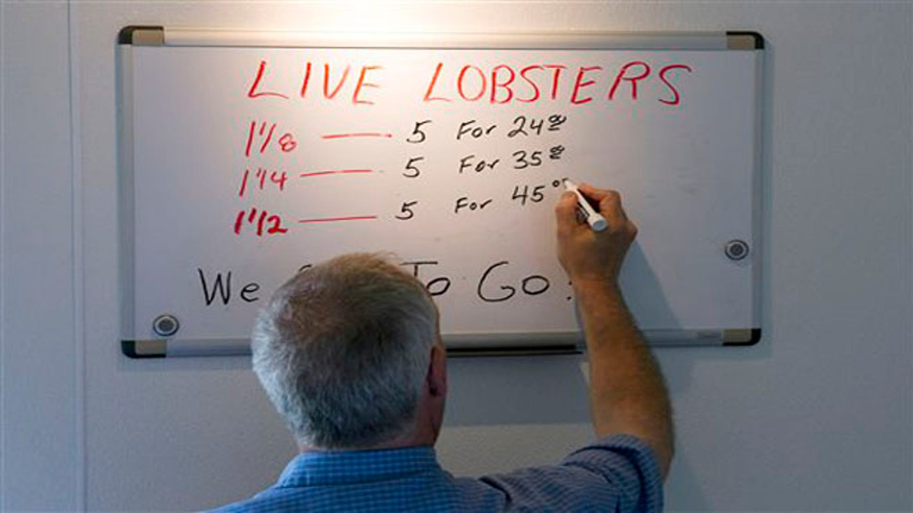 June 28, 2012: Bob Coppersmith updates the price board at Dock's Seafood Restaurant in South Portland, Maine. Many stores are selling the king of seafood for under $5 a pound, making it cheaper than bologna by weight.