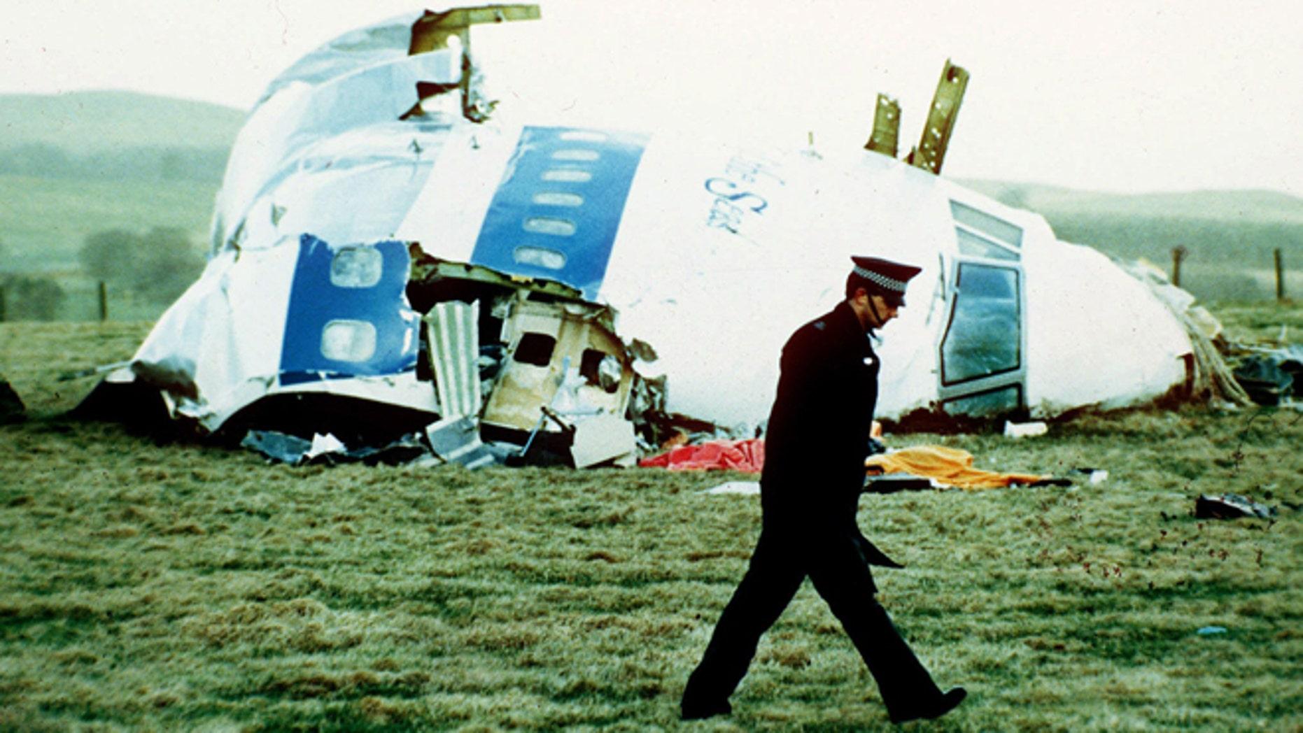 Un policía pasa frente a los restos del avión de Pan Am en Lockerbie, Escocia, el 21 de diciembre de 1988. Abdel Baset al-Megrahi, un libio encontrado culpable del atentado donde murieron 270 personas, murió a los 60 años debido al cáncer, se informó el domingo 20 de abril de 2012. (Foto AP/Martin Cleaver, Archivo)