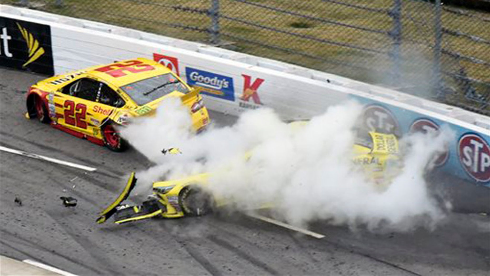 Joey Logano (22) and Matt Kenseth (20) tangle in Turn 1 during the NASCAR Sprint Cup Series auto race at Martinsville Speedway in Martinsville, Va., Sunday, Nov. 1, 2015. (AP Photo/Don Petersen)