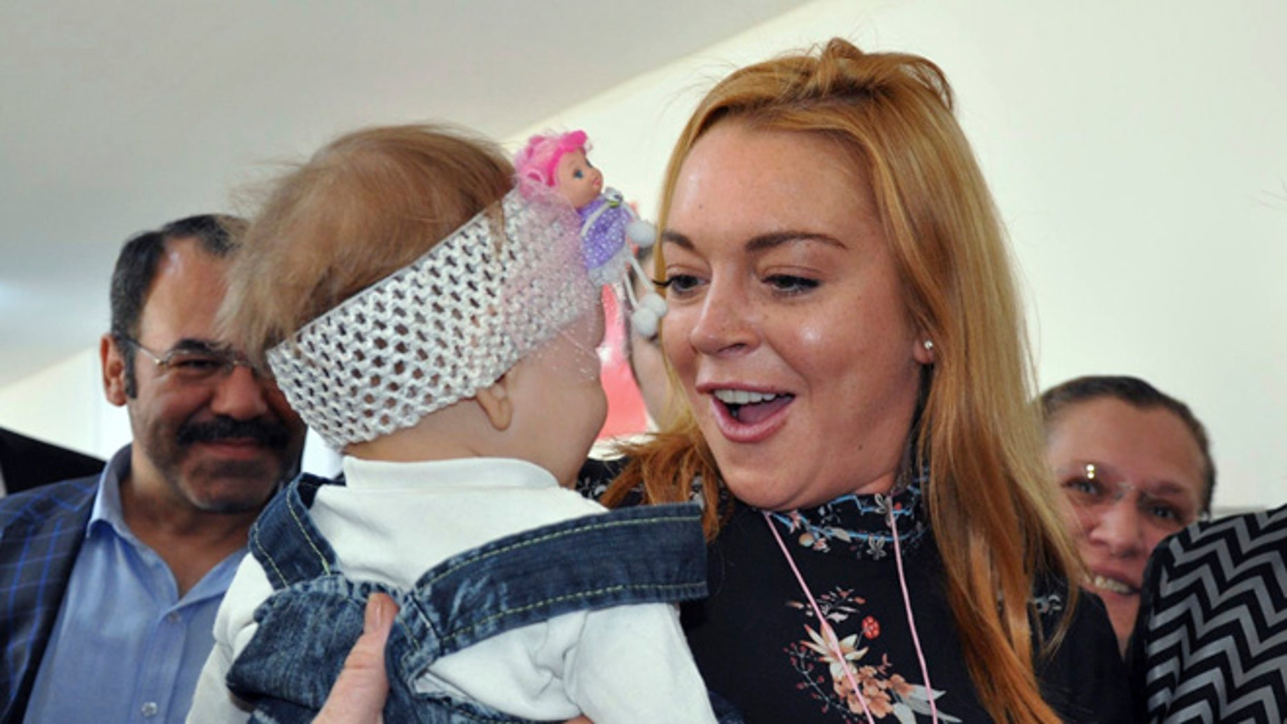 October 8, 2016. Lindsay Lohan holds a Syrian refugee child at a Turkish government-run Syrian refugee camp in Nizip.