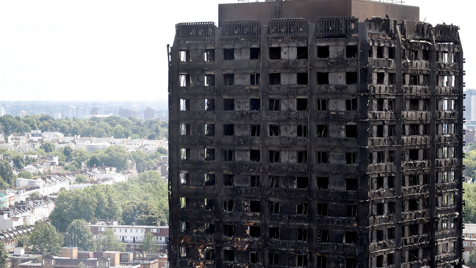 Firemen, left, inspect the scorched facade of the Grenfell Tower in London, Thursday, June 15, 2017, after a massive fire raced through the 24-storey high-rise apartment building in west London early Wednesday.  Firefighters are beginning the task of combing through the devastated apartment tower, checking integrity of the structure and searching to find victims.(AP Photo/Frank Augstein)