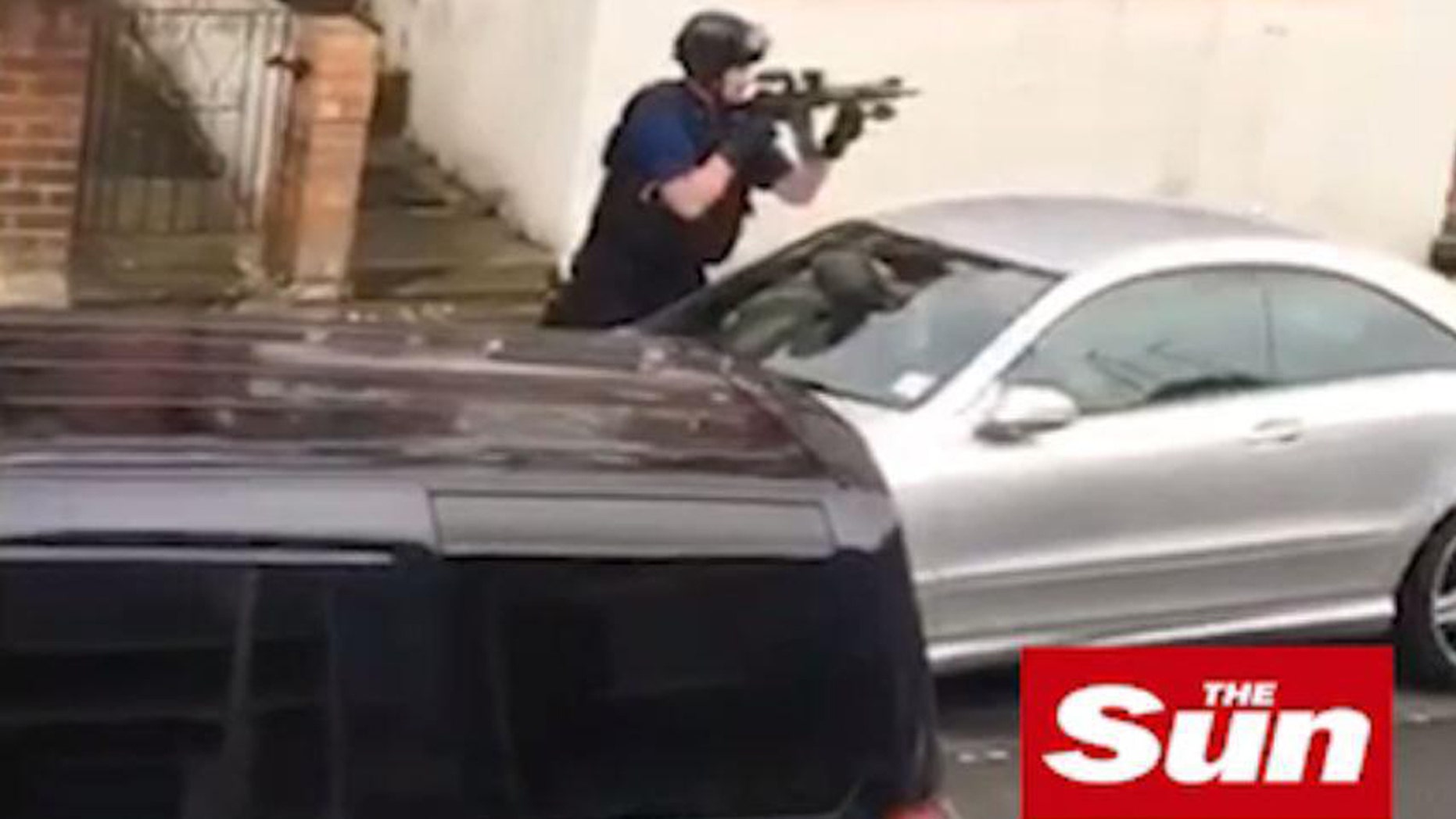 An armed cop is seen during a police raid in Willesden, northwest London