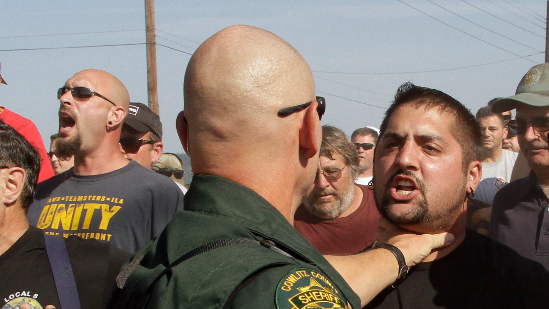 A Cowlitz County Sheriff grabs a union worker by the throat as police move in on several hundred union workers blocking a grain train in Longview, Wash., Wednesday, Sept. 7, 2011.
