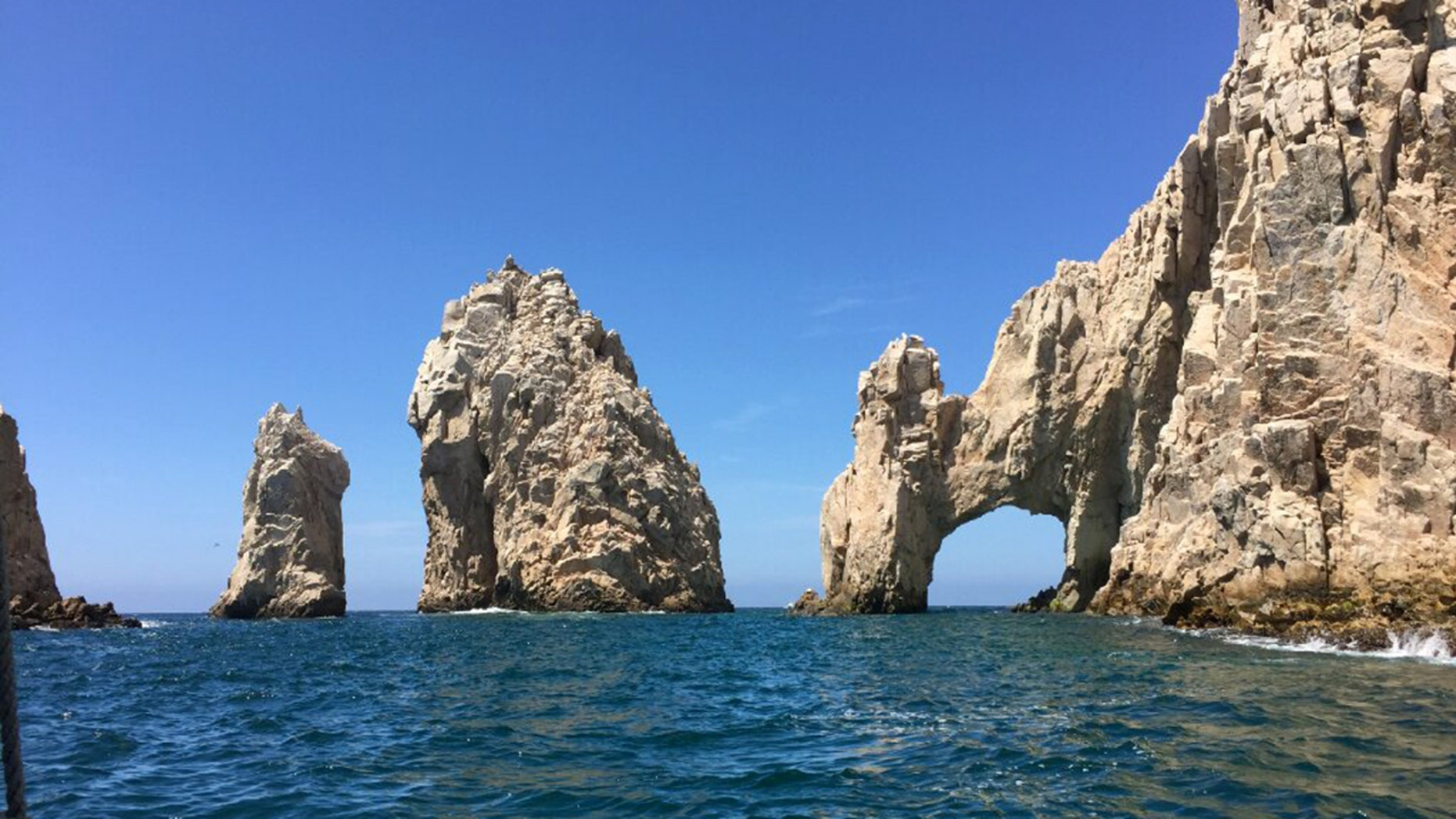 The distinctive landmark of Cabo San Lucas is the rugged taffy-colored El Arco (The Arch) rock formation that erupts from the sea at the tip of the Baja Peninsula, where the Pacific Ocean meets the Sea of Cortez.