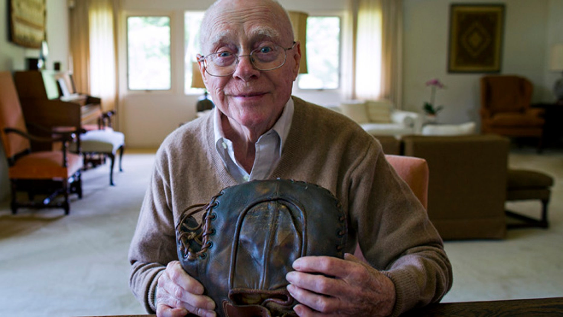 June 30, 2014: Howard Henderson, who as a boy in New York played catch with baseball legend Lou Gehrig, holds a signed baseman's mitt given to him by Gehrig when he was young, at Henderson's Greenwich, Conn., home.