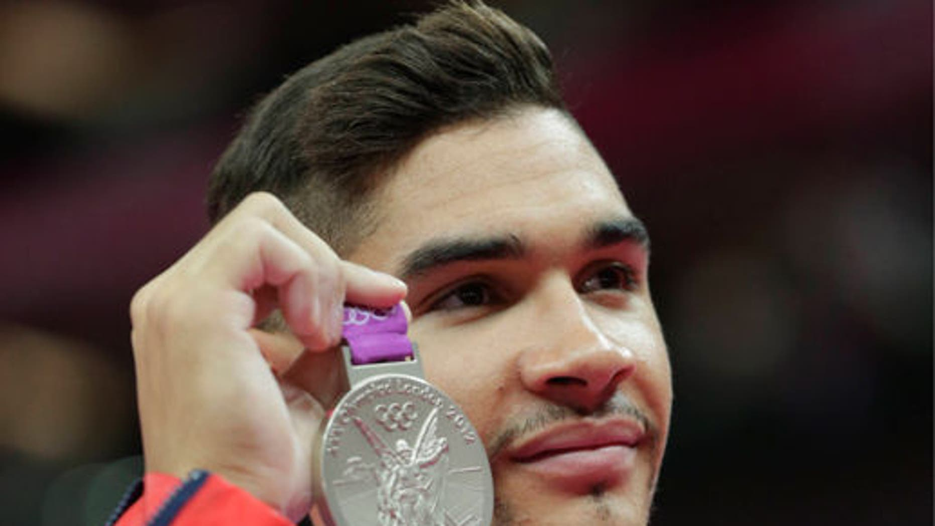 Louis Smith displays his silver medal during the artistic gymnastics men's pommel horse finals at the 2012 Summer Olympics.