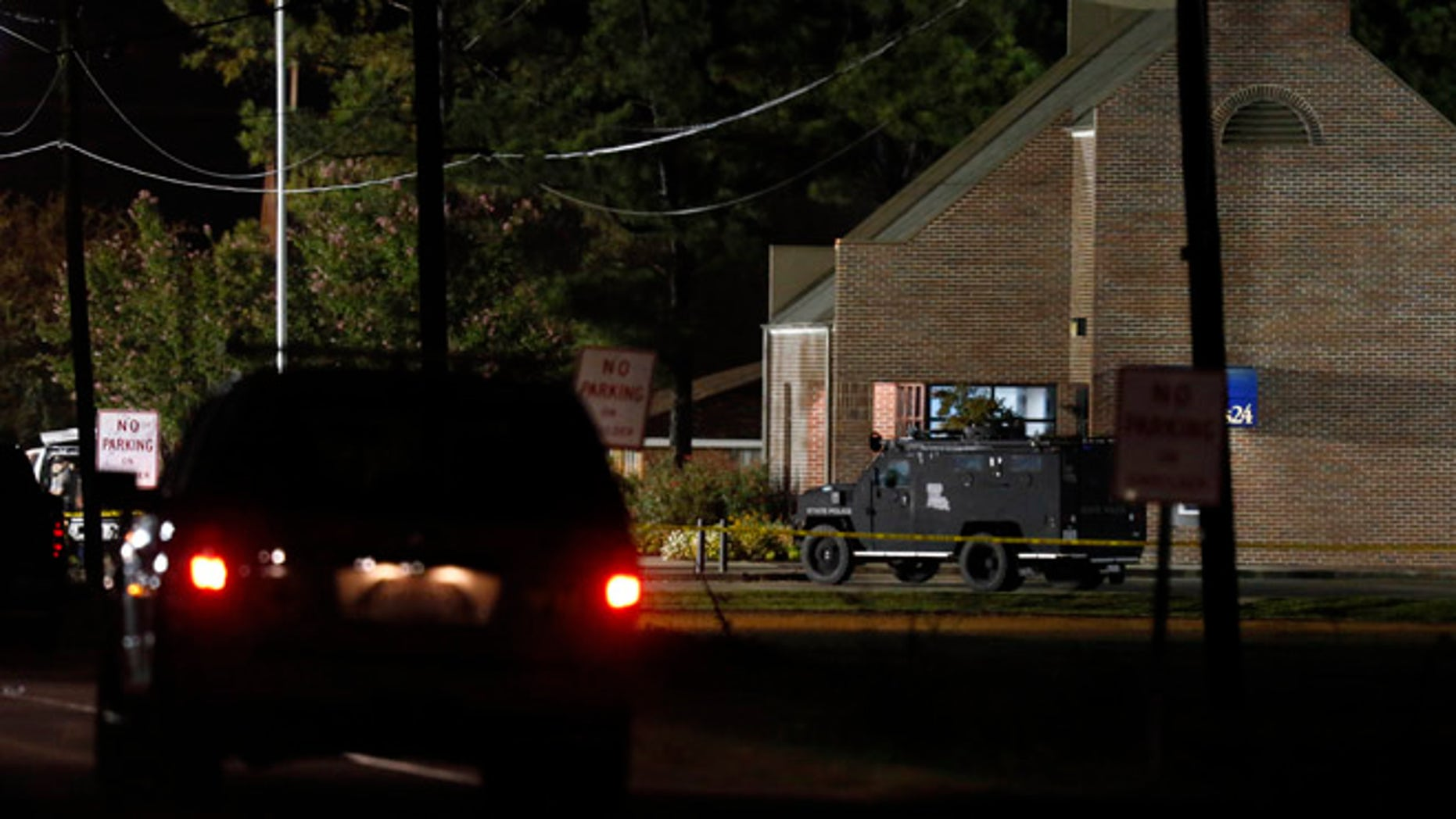 Aug. 14, 2013: Police drive past the Tensas State Bank branch in St. Joseph, La., early Wednesday morning in St. Joseph, La., where a gunman took three people hostage Tuesday.