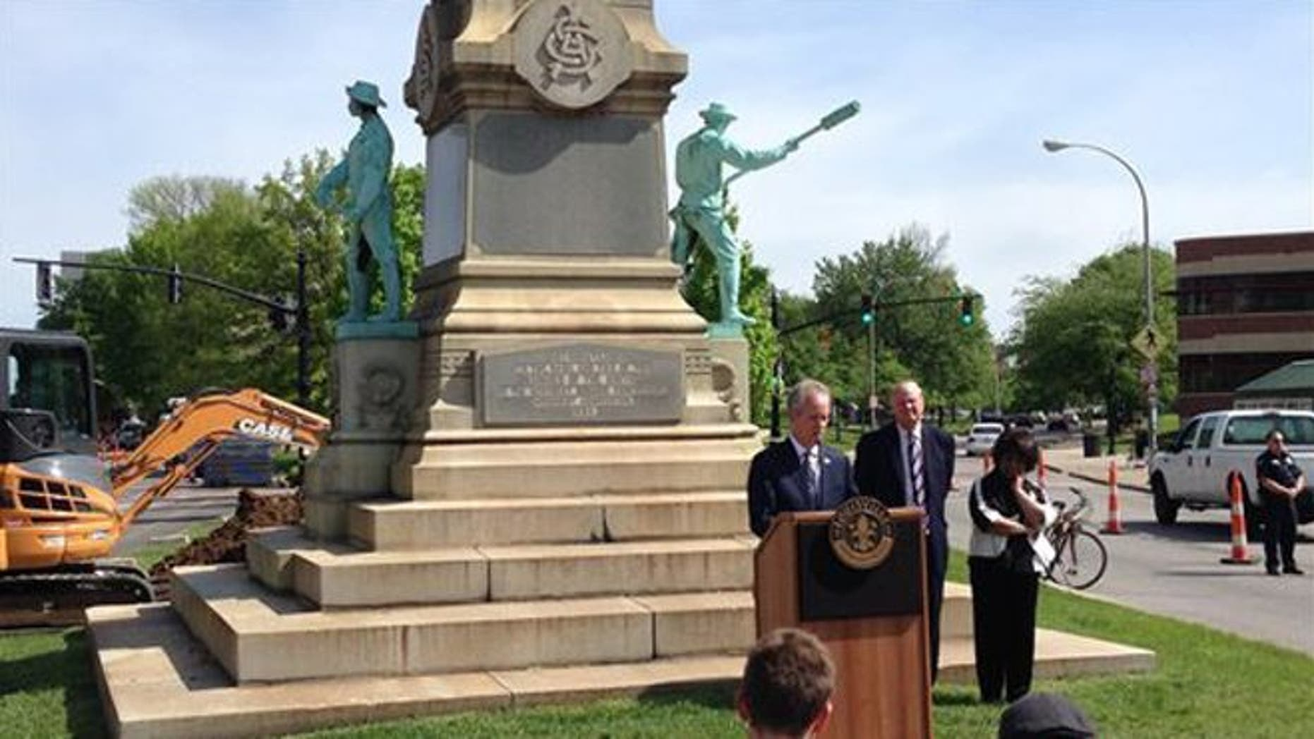 Louisville Mayor Greg Fischer speaks in front of the Confederate monument near the University of Louisville with university President James Ramsey, left, in Louisville, Ky., Friday, April 29, 2016. The Confederate monument capped with a statue of Jefferson Davis will be removed from a spot near the University of Louisville campus where it has stood since 1895. (AP Photo/Dylan Lovan)