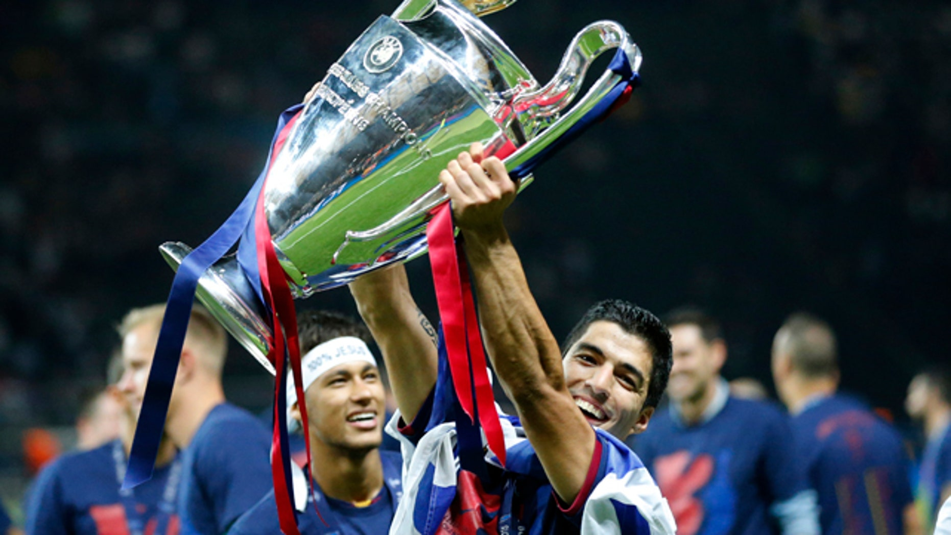 Barcelona's Luis Suarez and Neymar celebrates with the trophy after after the Champions League final soccer match between Juventus Turin and FC Barcelona at the Olympic stadium in Berlin Saturday, June 6, 2015. Barcelona won the match 3-1.  (AP Photo/Frank Augstein)
