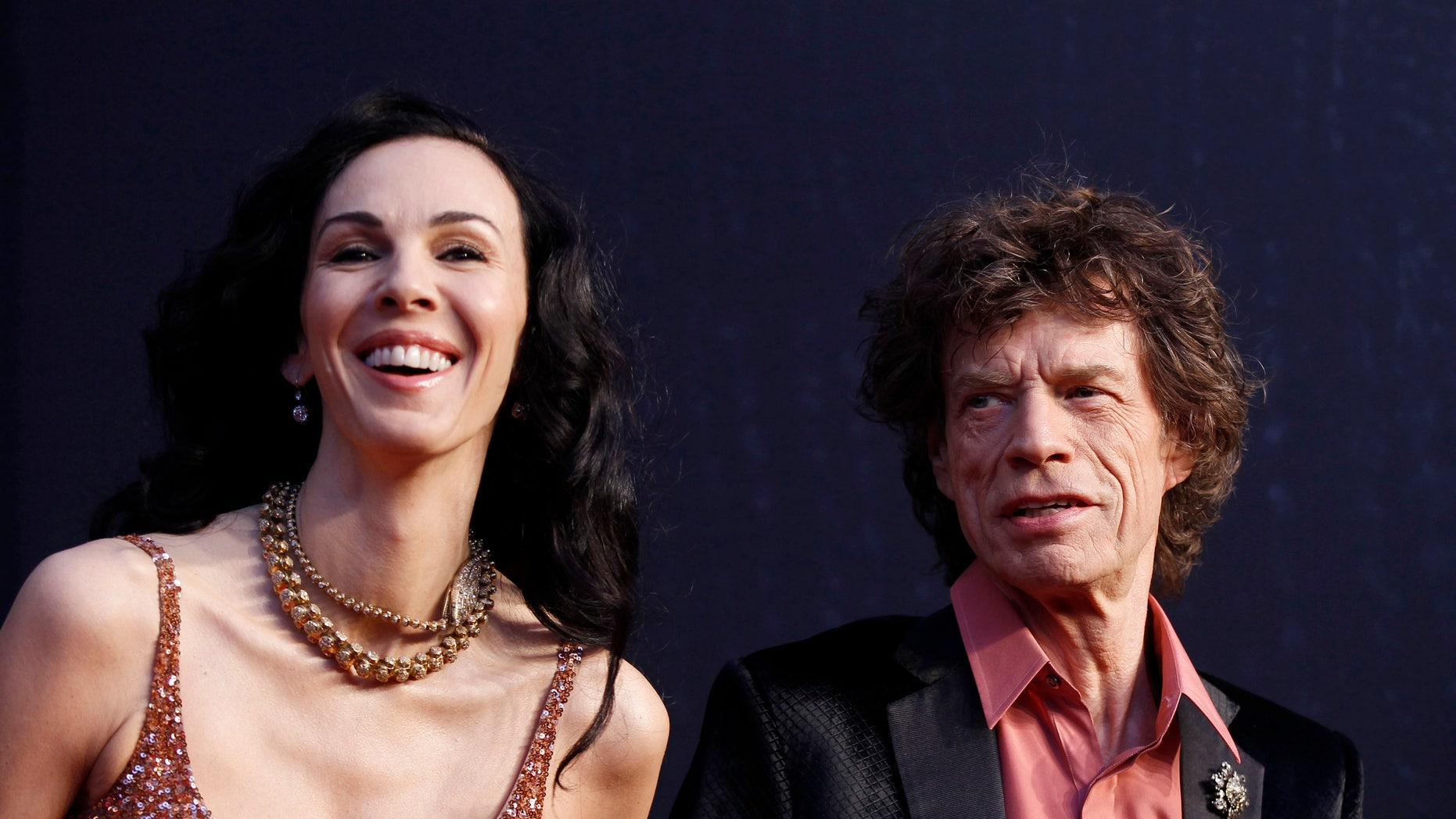 February 27, 2011. Rock musician Mick Jagger (R) and model L'Wren Scott arrive at the 2011 Vanity Fair Oscar party in West Hollywood, California.