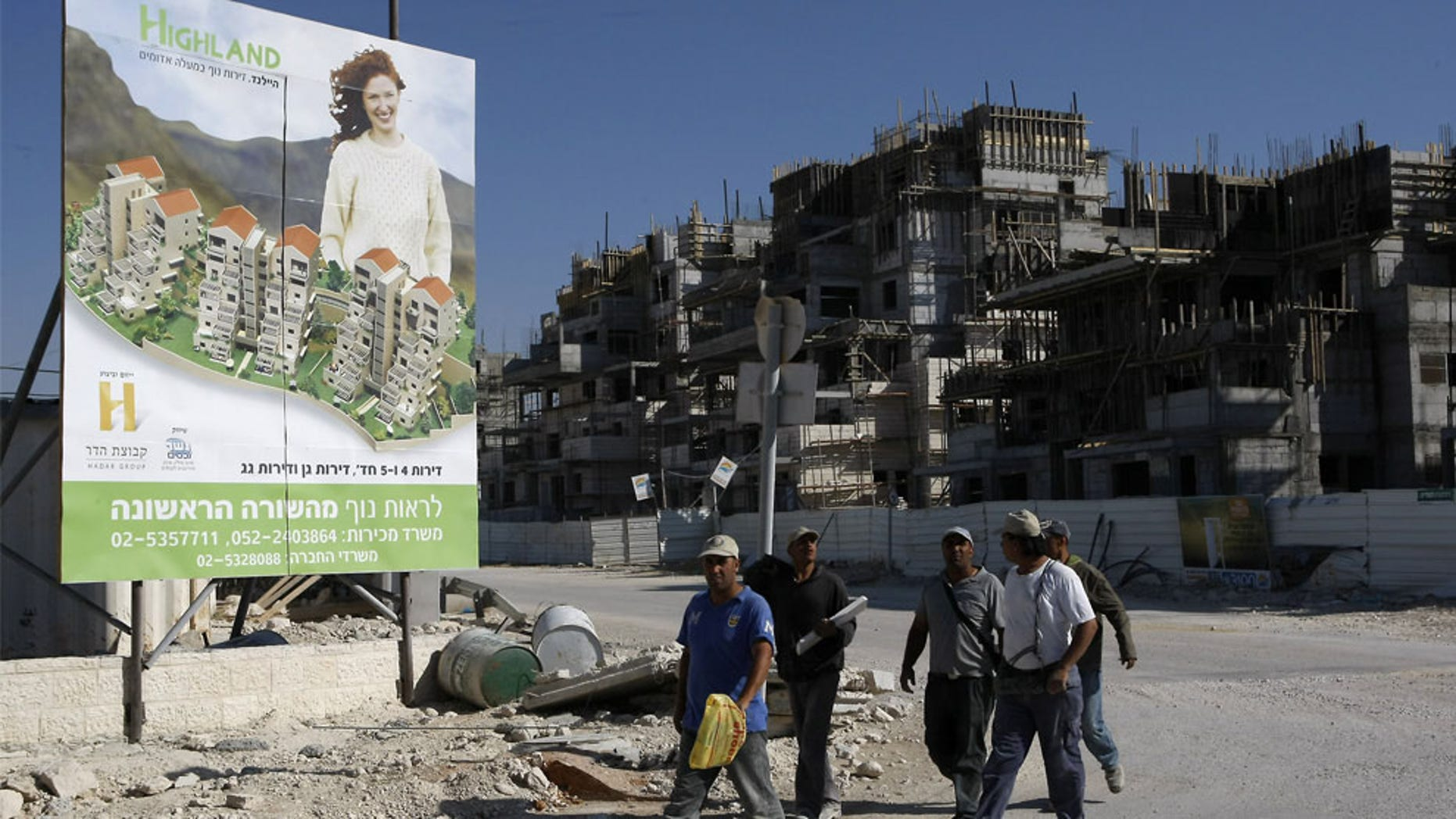 FILE: Palestinian laborers walk past a billboard advertising a new housing project in the Jewish settlement of Maale Adumim in the occupied West Bank. (AFP)