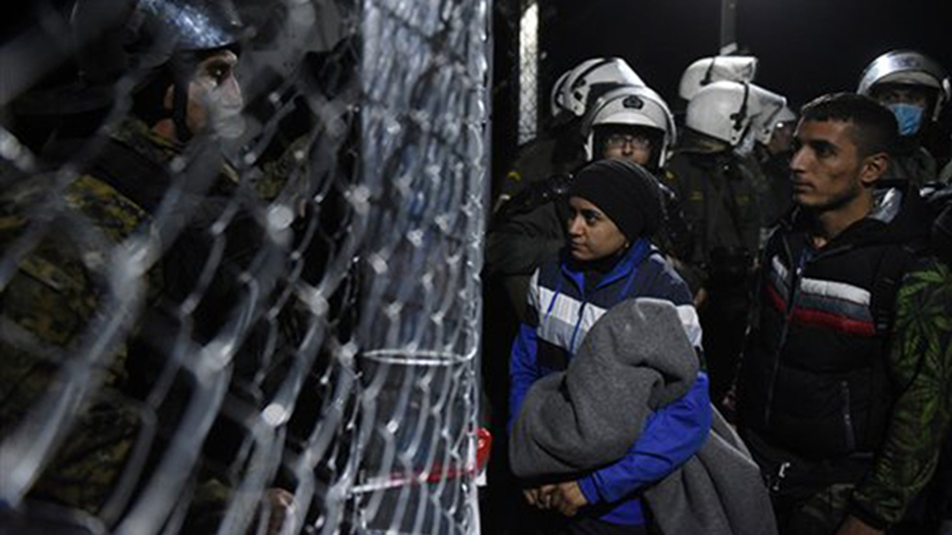 Refugees wait to cross the Greek-Macedonian border as policemen from both sides stand guard, near the northern Greek village of Idomeni, Thursday, Dec. 3, 2015. Greek riot police struggled to restore order Thursday after chaotic clashes between asylum-seekers at the country's border with Macedonia. (AP Photo/Giannis Papanikos)