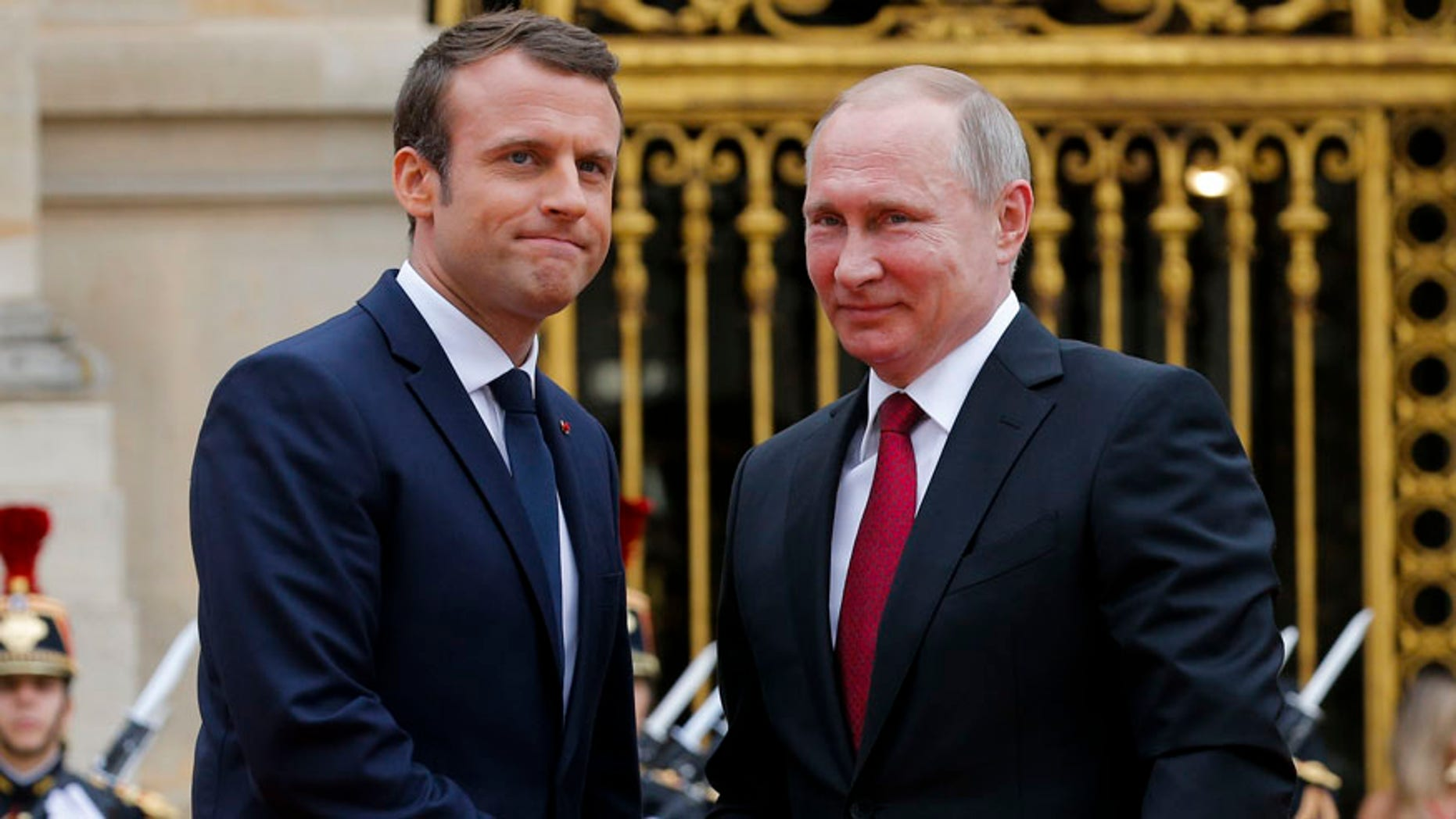 May 29, 2016: Russian President Vladimir Putin, right, is welcomed by French President Emmanuel Macron at the Palace of Versailles, near Paris, France.
