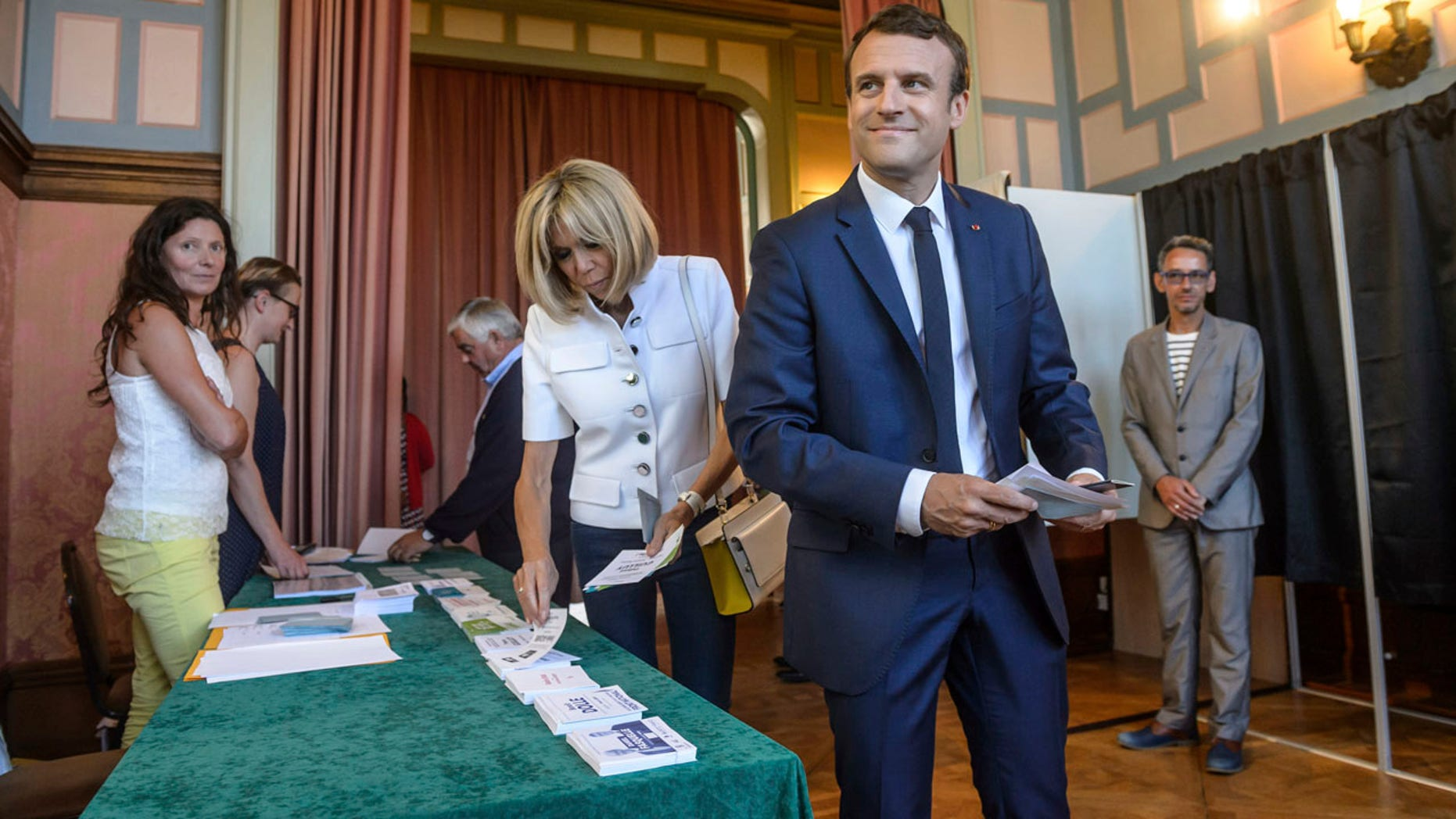 """French President Emmanuel Macron and his wife Brigitte Macron pick up ballots before voting in the first round of the two-stage legislative elections in Le Touquet, northern France, Sunday, June 11, 2017. French voters are choosing legislators in the first round of parliamentary elections, with President Emmanuel Macron's party """"Republic on the Move"""" hoping to win a strong majority in the National Assembly to push through bold labor and security reforms. (Christophe Petit-Tesson/Pool Photo via AP)"""