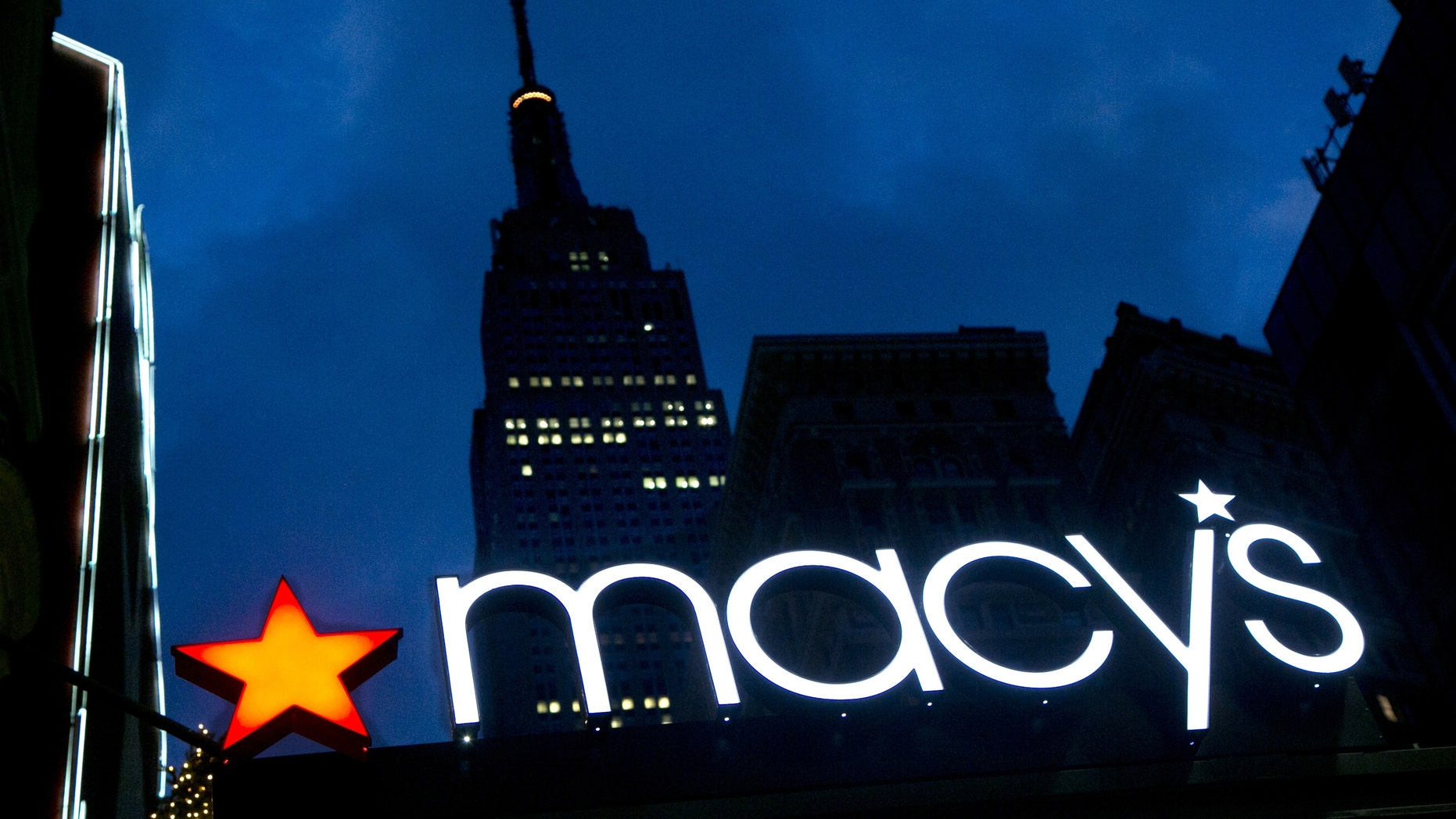 The Macy's logo is illuminated with the Empire State Building in the background