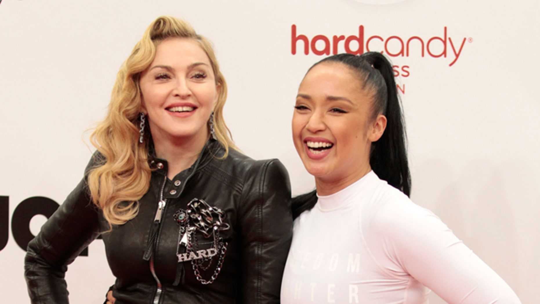 October 17, 2013. U.S. singer Madonna (L) poses with her personal fitness trainer Nicole Winhoffer to promote her latest gym in her Hard Candy Fitness centre chain in Berlin.
