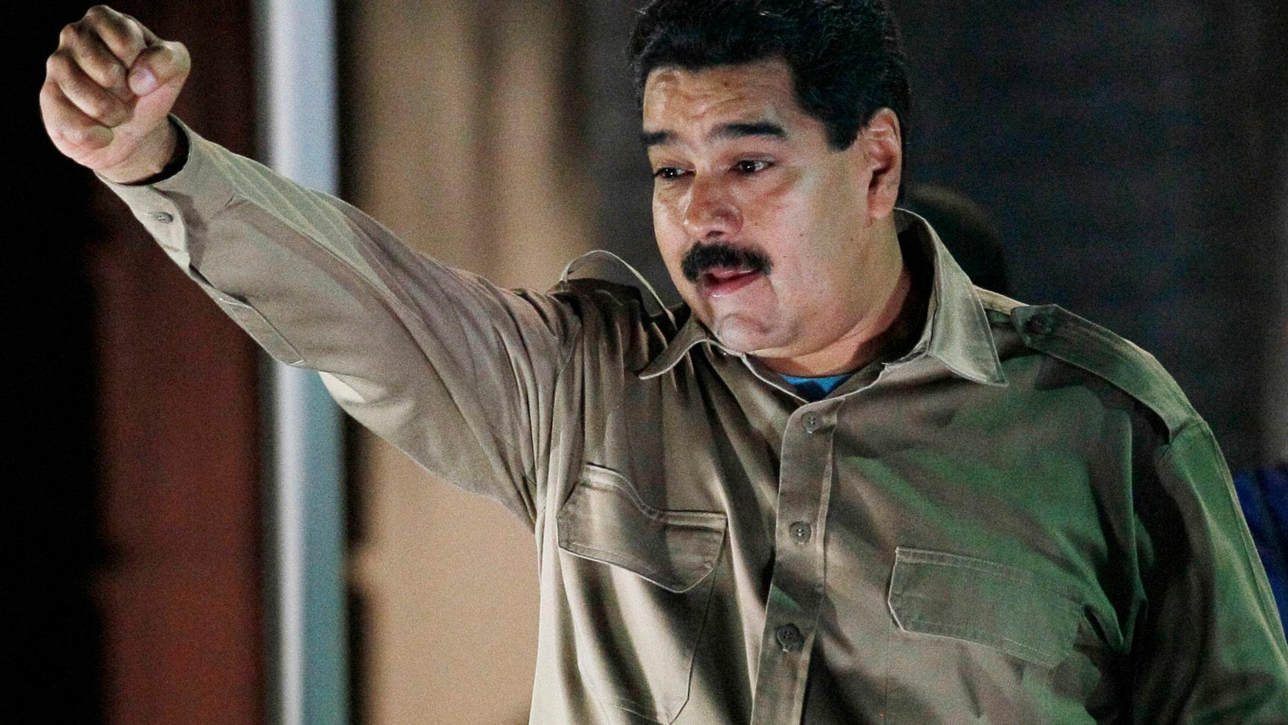 El presidente de Venezuela Nicolás Maduro sostiene los documentos que le otorgan facultades para gobernar por decreto mientras saluda a simpatizantes en el palacio presidencial de Miraflores, en Caracas, Venezuela, el martes 19 de noviembre de 2013. Maduro promulgó dos días después las dos primeras leyes. (AP Foto/Ariana Cubillos)