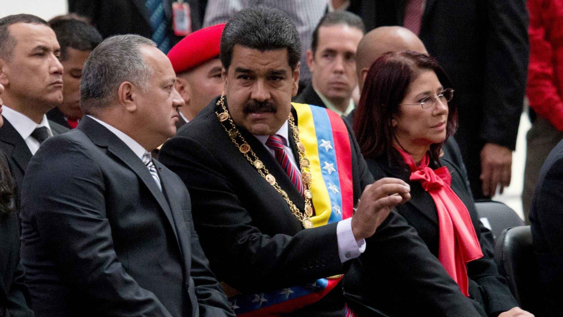 El presidente venezolano Nicolás Maduro, al centro, habla con Diosdado Cabello, presidente de la Asamblea Nacional, izquierda, durante una ceremonia para conmemorar el 185to aniversario de la muerte del héroe independentista Simón Bolivar en Caracas, Venezuela, el jueves 17 de diciembre de 2015. La mujer a la derecha es la primera dama Cilia Flores. (Foto AP/Fernando Llano)