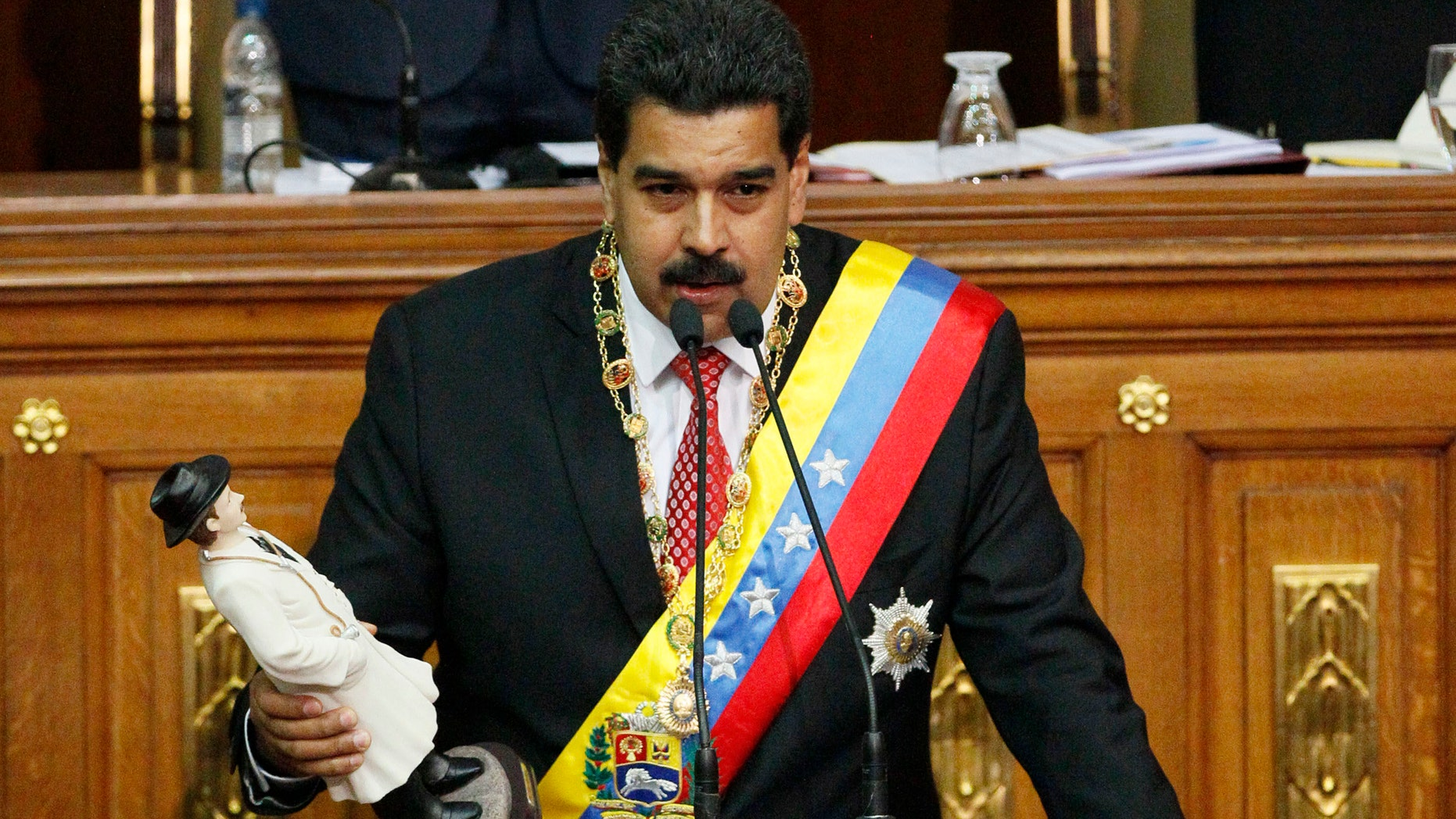 Maduro holds a statue of the beloved physician folk-saint Dr. Jose Gregorio Hernandez as he delivers a speech at the National Assembly in Caracas, Venezuela, Tuesday, Oct. 8, 2013.