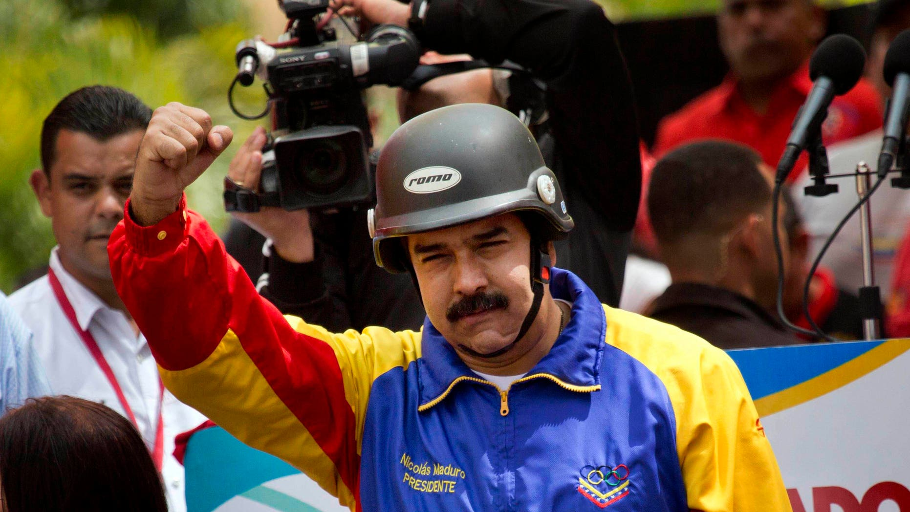 A helmet wearing Venezuelan President Nicolas Maduro cheers motorcyclists during a rally in support of his government in Caracas, Venezuela, Monday, Feb. 24, 2014. Since Feb. 12, opponents of President Nicolas Maduro have been staging countrywide protests that the government says have resulted in scores of deaths and more than more than a hundred injured. The demonstrators blame Maduro's administration for the country's high crime rate and economic troubles. (AP Photo/Rodrigo Abd)