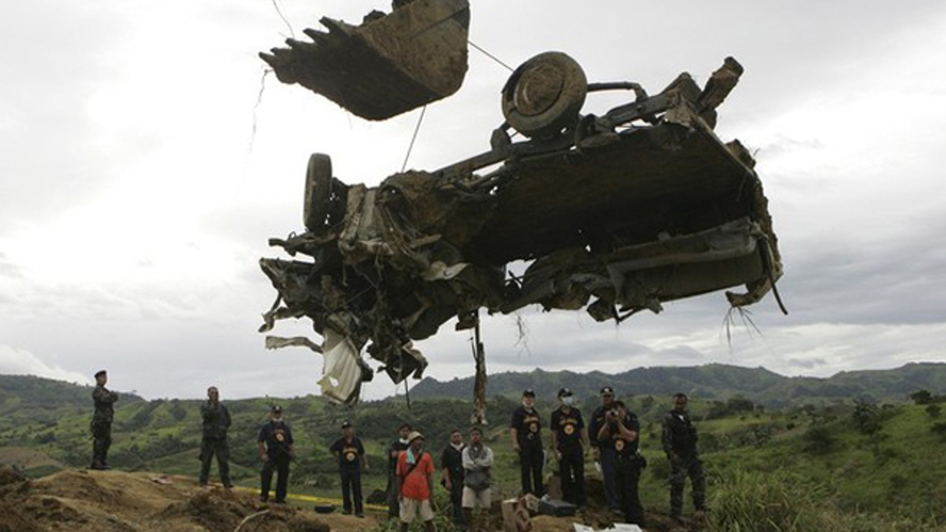A backhoe lifts the wreckage of a local television network's vehicle that was unearthed from a shallow grave at the site of a massacre of a political clan that included several journalists in the outskirts of Ampatuan, Maguindanao in southern Philippines in this November 25, 2009 file photo. The 2009 massacre of 57 people, including 31 journalists, in the southern province of Maguindanao was horrific even by the standards of the Philippines, whose restive south is riven by political and insurgent violence.