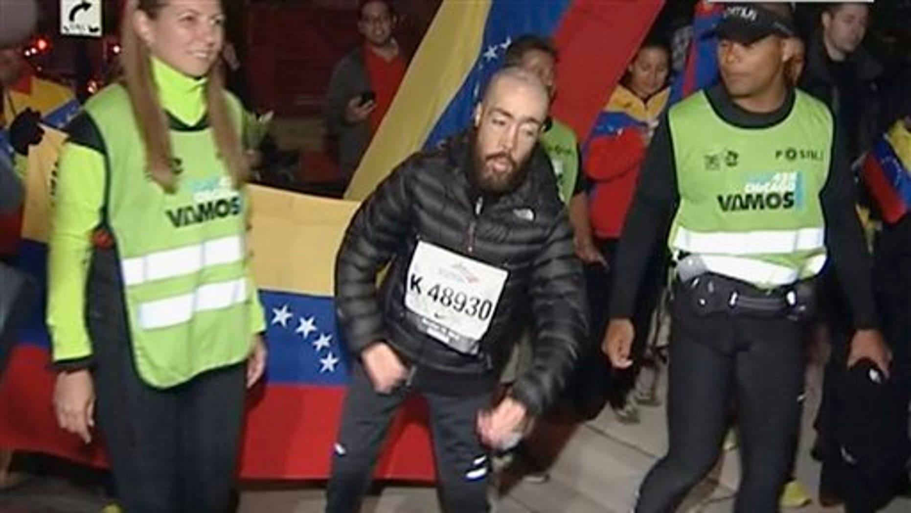 This photo from video provided by Ken Herzlich of Embargo Chicago shows Maickel Melamed, 38, center, of Venezuela, who has muscular dystrophy, nearing the finish line early Monday, Oct. 14, 2013, to be the last runner to finish the Chicago Marathon.