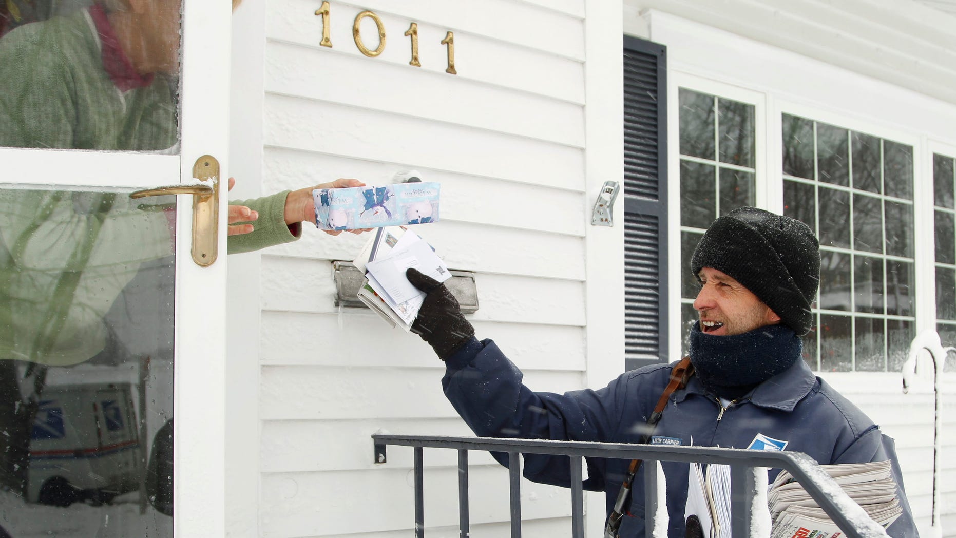 FILE: Dec. 20, 2012: Mail carrier Mike Perkins delivers mail in the snow along Fletcher Avenue in Waterloo, Iowa.