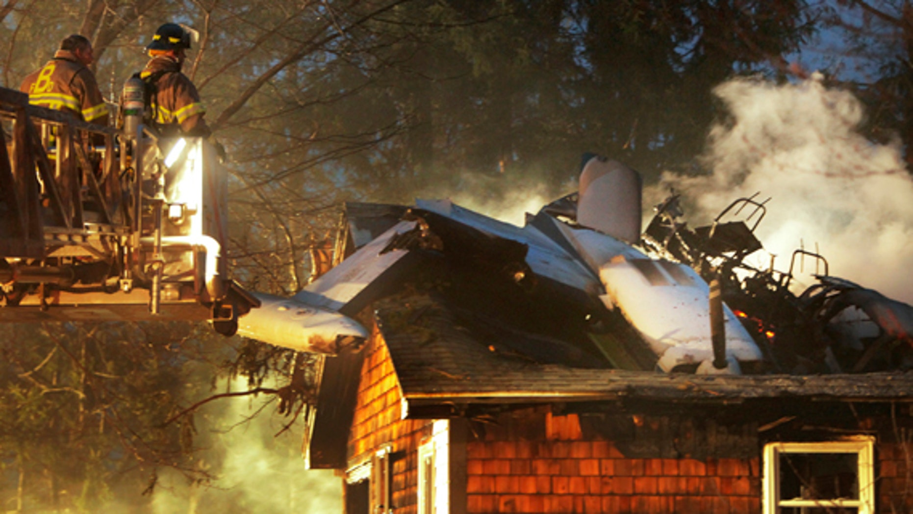 April 10: Firemen work at the scene where a small plane crashed into a house near the Biddeford, Maine