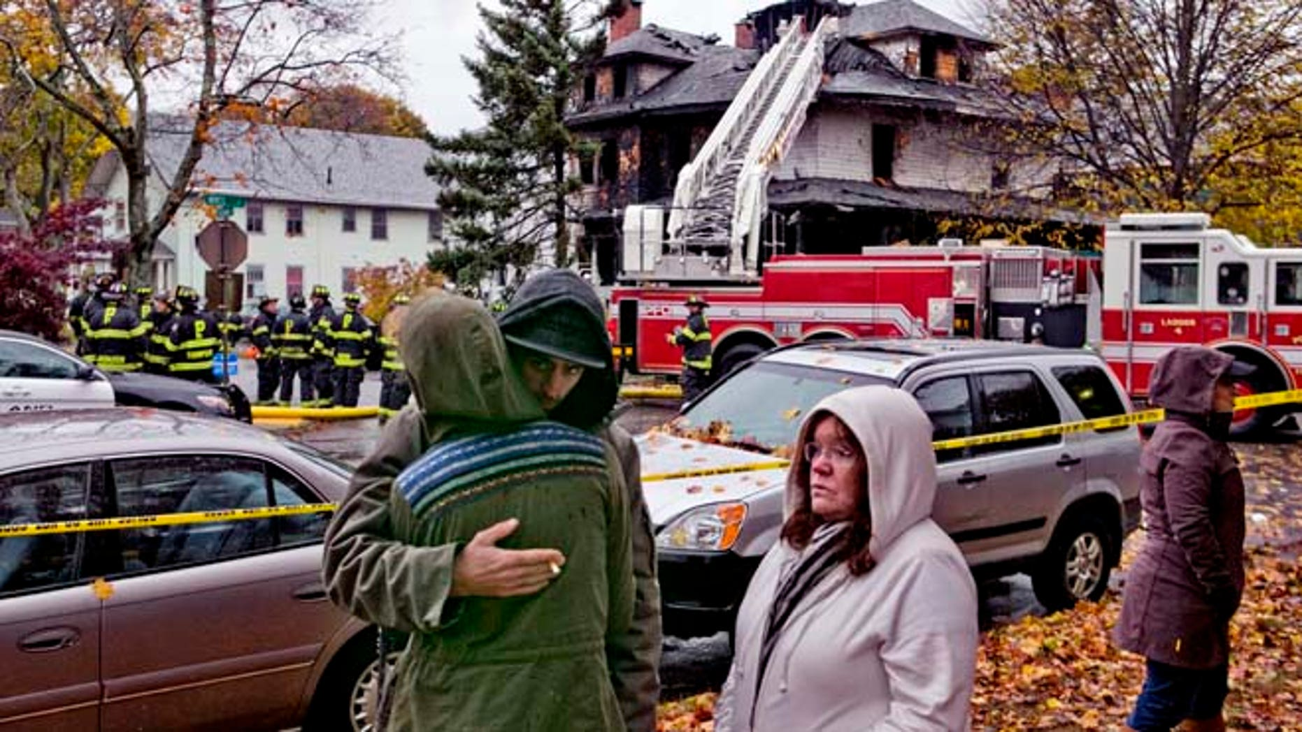 Nov. 1, 2014: Friends of a victim of a fatal apartment building fire console each other in Portland, Maine. (AP)
