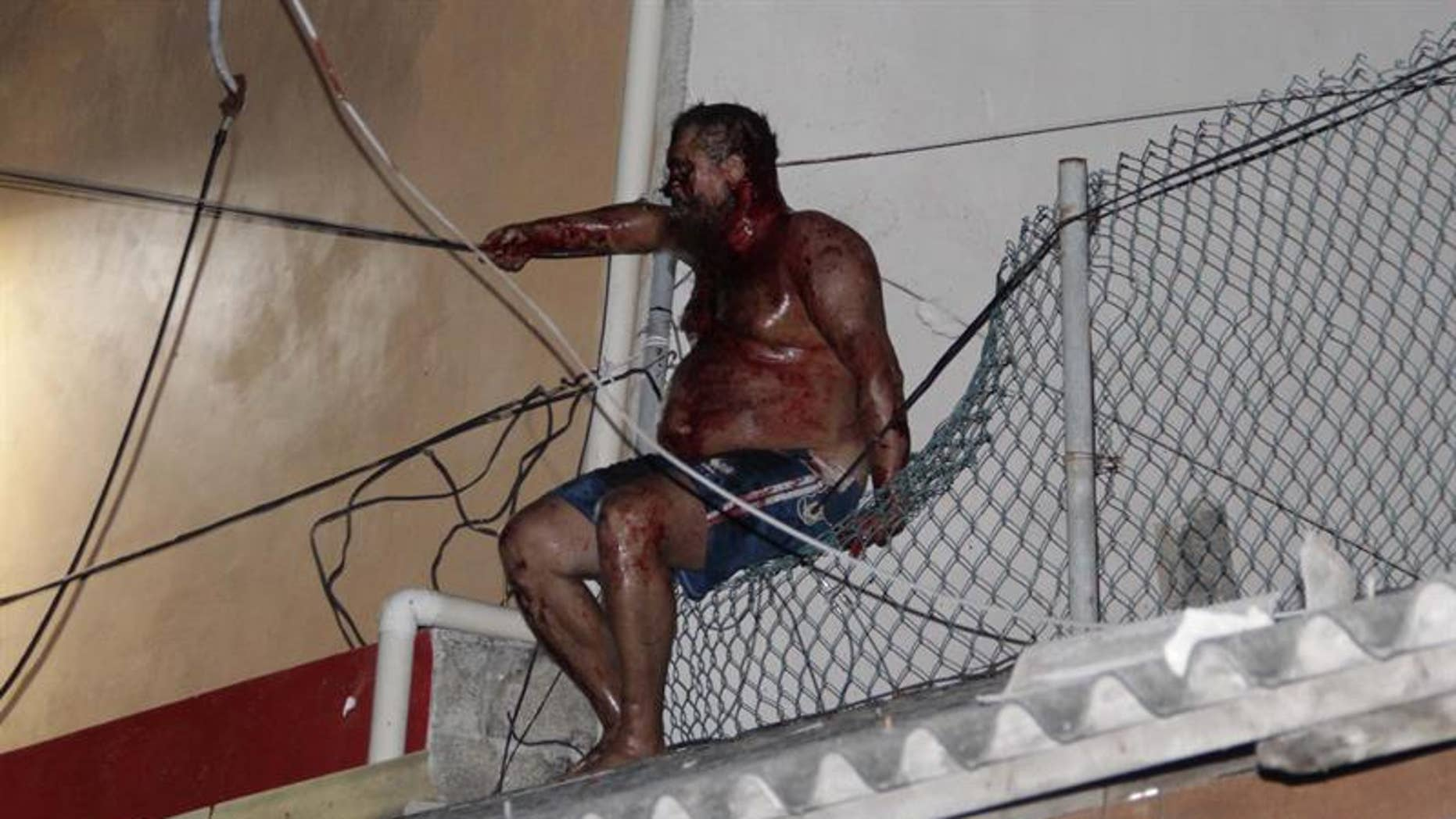 Aleksey Makeev sits on a fence on top of a building after being beaten by an angry mob on May 19, 2017.