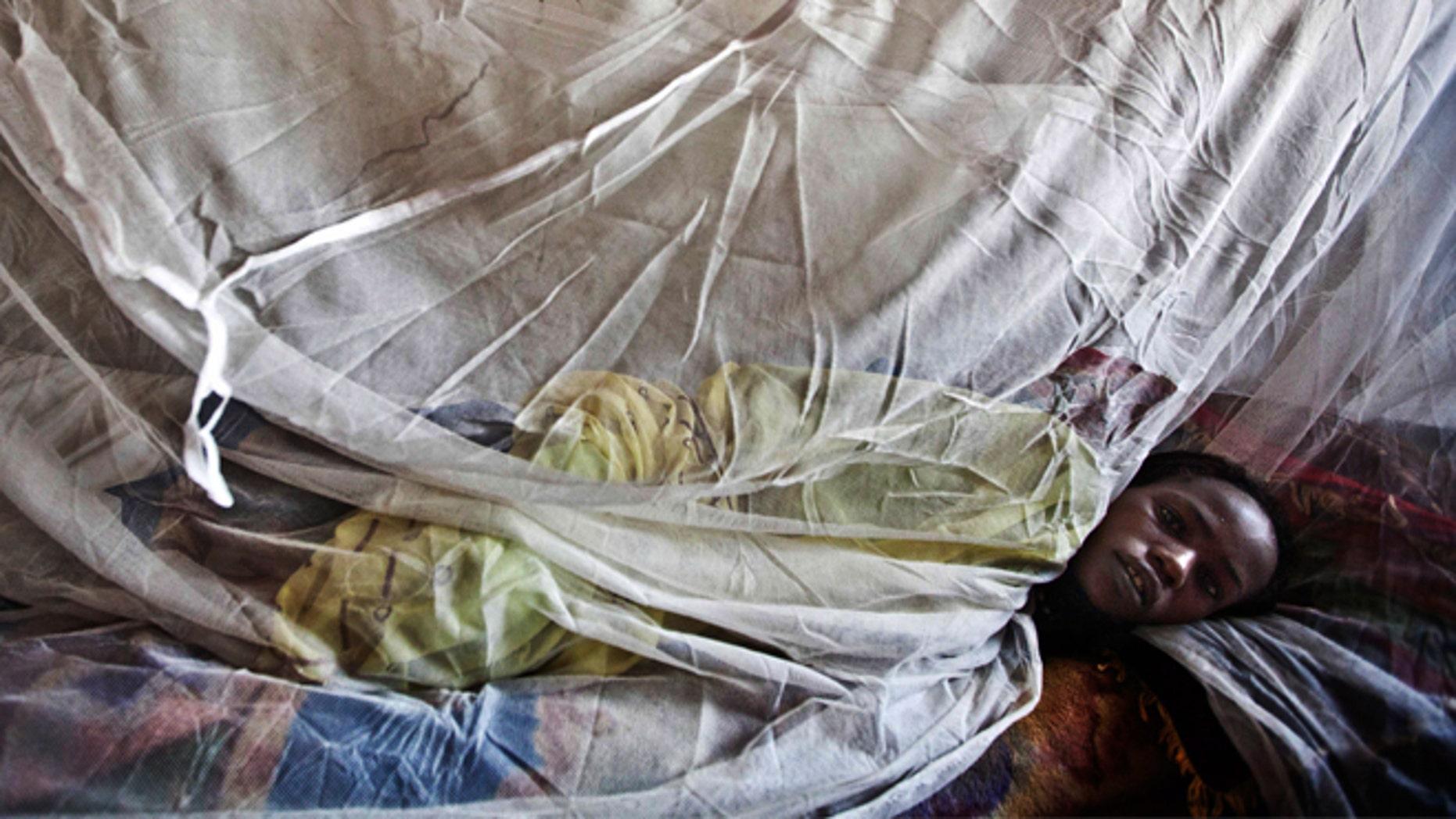 A woman suffering from malaria rests on a bed at a hospital in El Sereif village, North Darfur, Sudan. (AP Photo/UNAMID, Albert Gonzalez Farran, File)