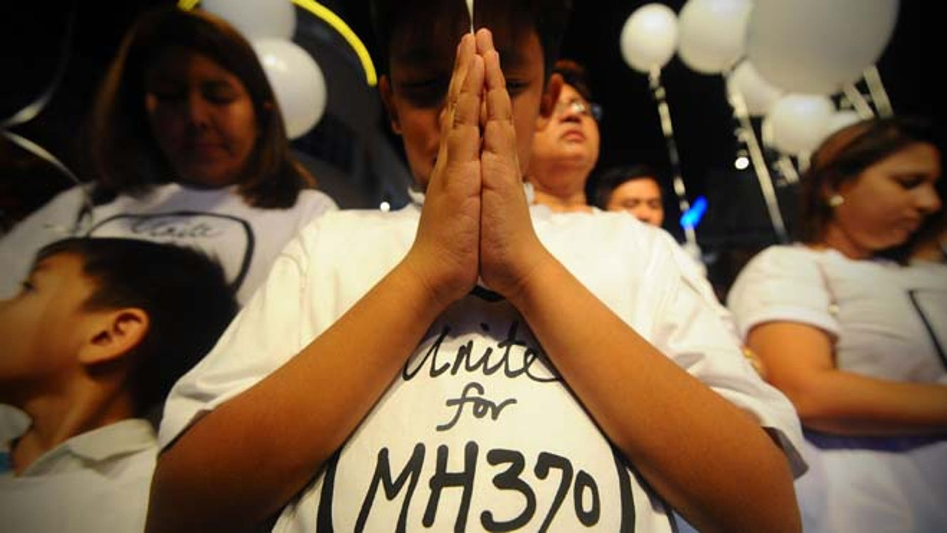 March 18, 2014: A young Malaysian boy prays at an event for the missing Malaysia Airline Flight 370 at a shopping mall in Petaling Jaya on the outskirts of Kuala Lumpur, Malaysia.