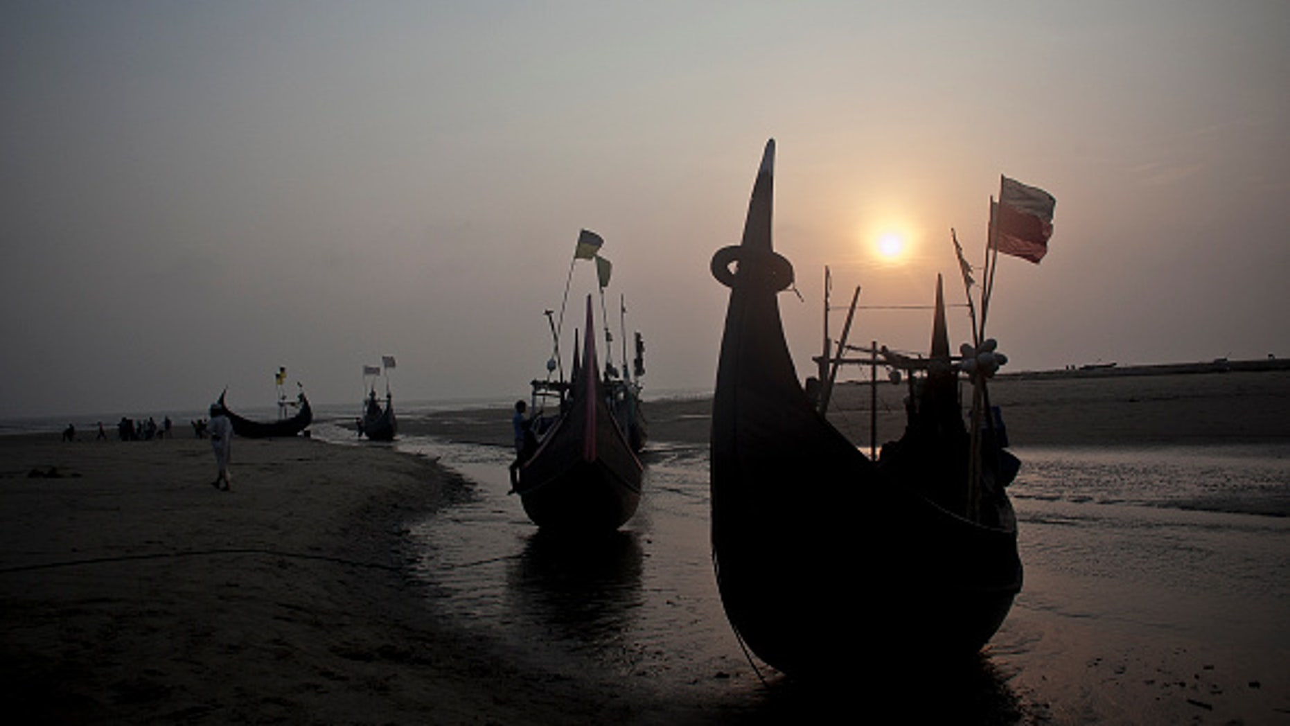 SHAMLAPUR, BANGLADESH - JULY 4:  Fishing boats, like the kind that traffickers use, are seen on the beach July 4, 2015 in Shamlapur, Bangladesh. In the past months thousands of Rohingya have landed on the shores of Indonesia, Malaysia and Thailand, many of them by way of Bangladesh. The Rohingya pay up to $2,000 to traffickers, and they sail out from Bangladesh's southern coastline on fishing boats to meet larger ships in the deep sea that will take them to Malaysia. UNHCR estimates that there are more than 300,000 Rohingya living in Bangladesh. (Photo by Shazia Rahman/Getty Images)