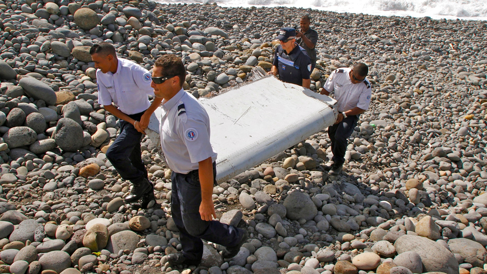July 29, 2015: French police officers carry a piece of debris from a plane known as a flaperon in Saint-Andre, Reunion Island. The barnacle-encrusted part was the first trace found of Malaysia Airlines Flight 370, which disappeared two years ago.