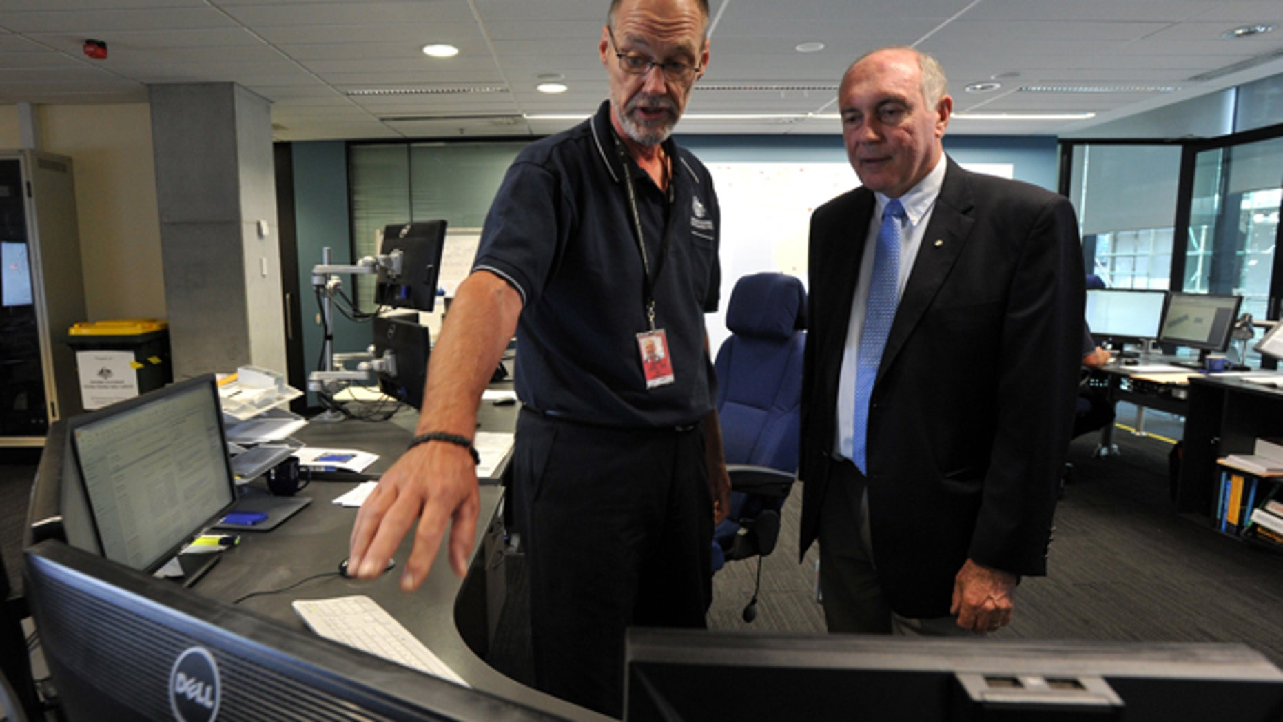 In this March 23, 2014 photo, Australian Deputy Prime Minister Warren Truss, right, talks with John Rice, senior search and rescue officer and mission coordinator for the search for the missing Malaysia Airlines Flight MH370, at rescue coordination center of the Australian Maritime Safety Authority in Canberra. Just weeks before the hunt for the missing Malaysian airliner is set to resume, an Australian official said Thursday, Aug. 28, that the sprawling search area in the southern Indian Ocean may be extended farther south based on a new analysis of a failed attempt to call the plane by satellite phone.