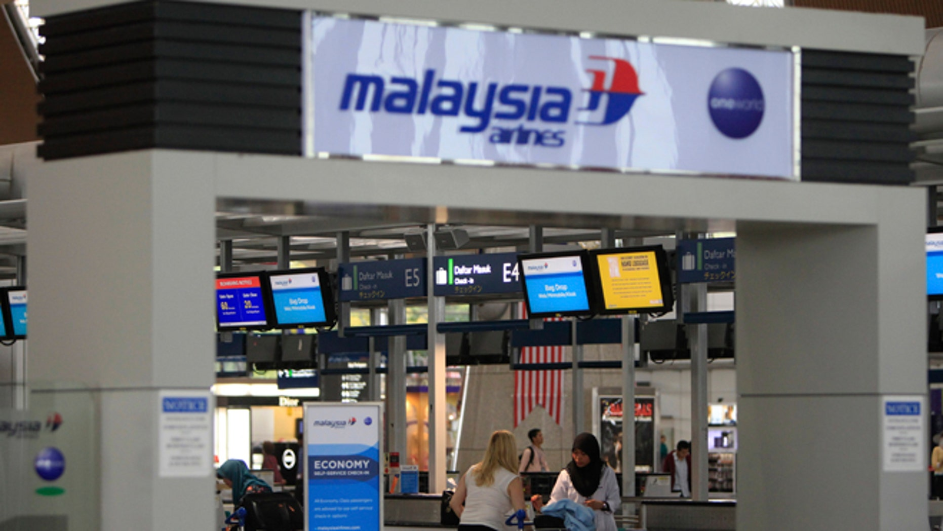 Aug. 29, 2014: Passengers are ready to check in at a departure lobby at Kuala Lumpur International Airport in Sepang, Malaysia. Malaysia Airlines will cut 6,000 workers as part of an overhaul announced Friday to revive its damaged brand after being hit by double passenger jet disasters.(AP/Lai Seng Sin)
