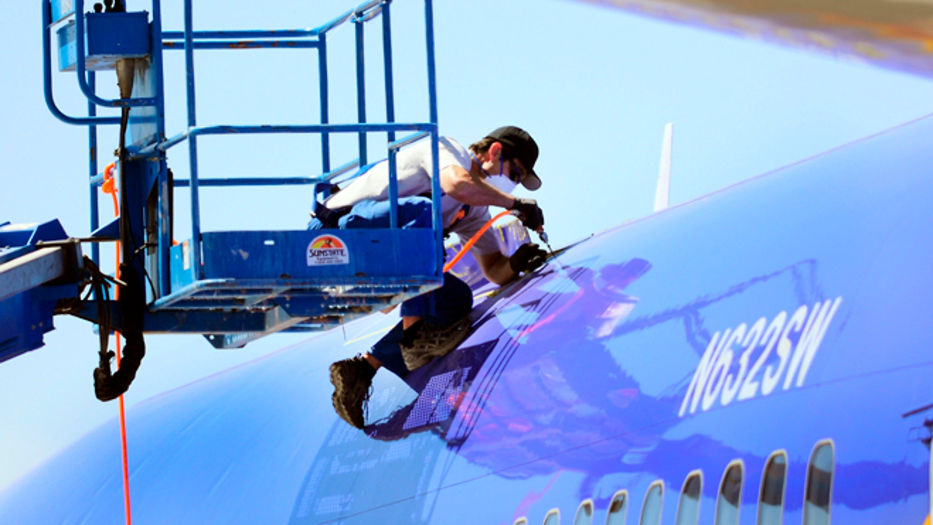 April 3, 2011: This photo shows a member of the National Transportation and Safety Board investigating the emergency landing of Southwest Airlines flight 812 cutting away a portion of the planes fuselage in Yuma, Ariz.